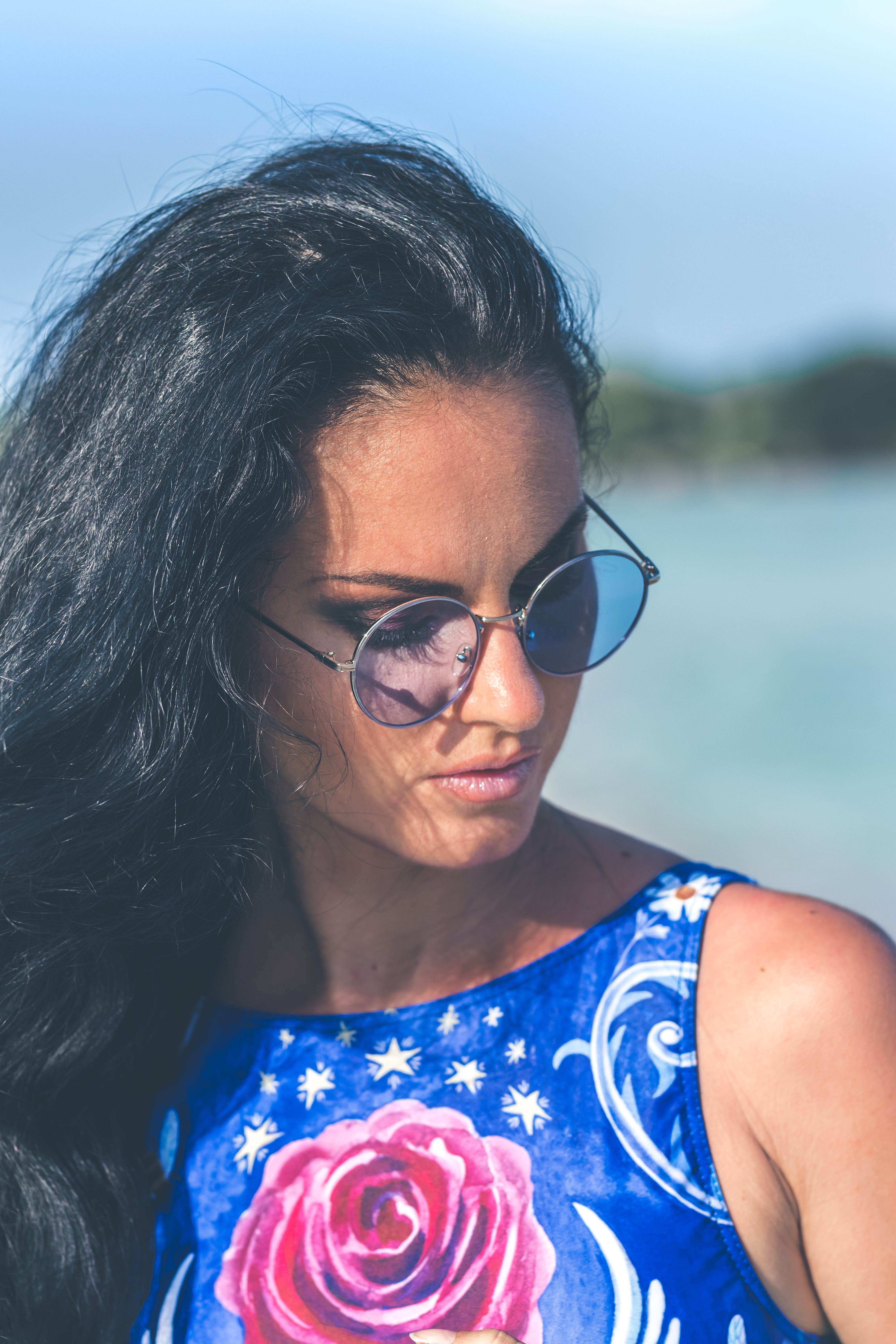 Shallow Focus Photography of Woman Wearing Blue Floral Sleeveless Top and Black Sunglasses With Gray Frames