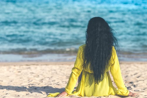 Woman Sitting Near Ocean