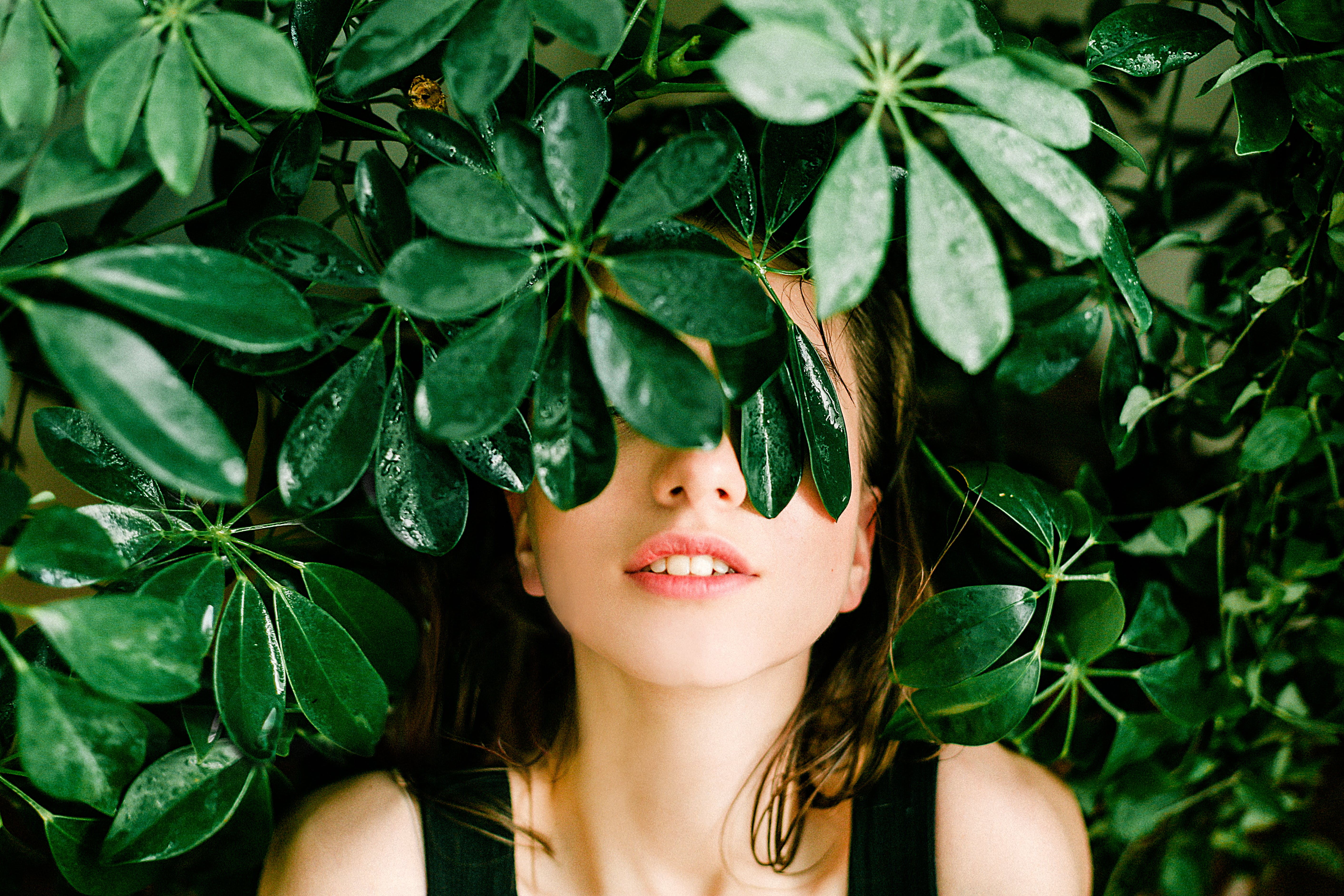 Woman in Black Top Beside Green Leafed Plant