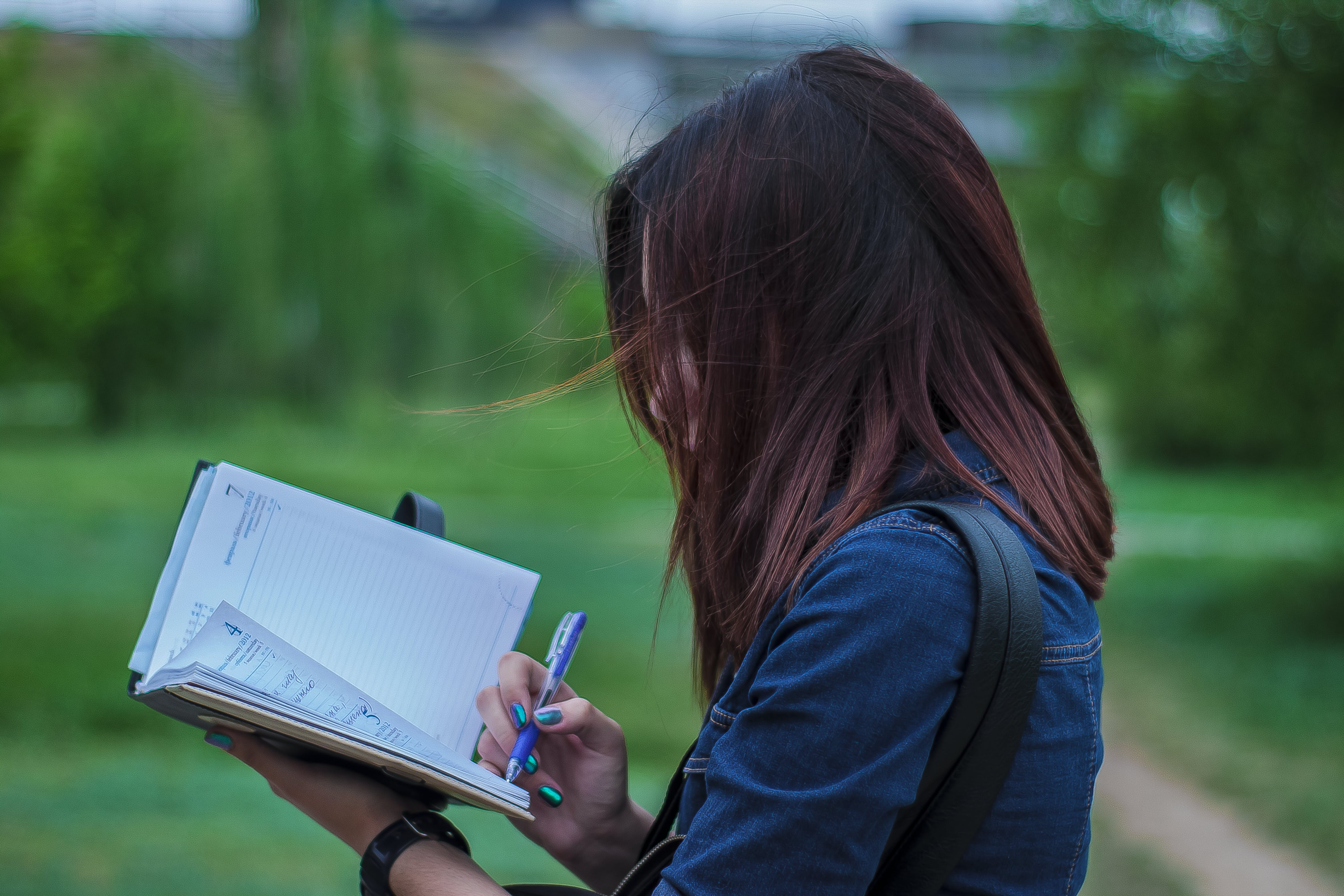 Close-Up Photography of a Person Writing on Notebook