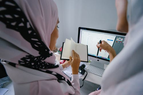Woman in Pink Headscarf Stands in Front of Silver Imac