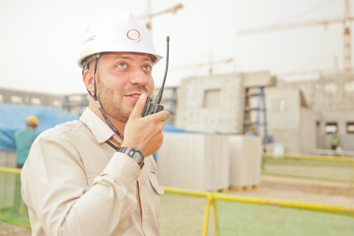 Man Wearing White Hard Hat Holding 2-way Radio