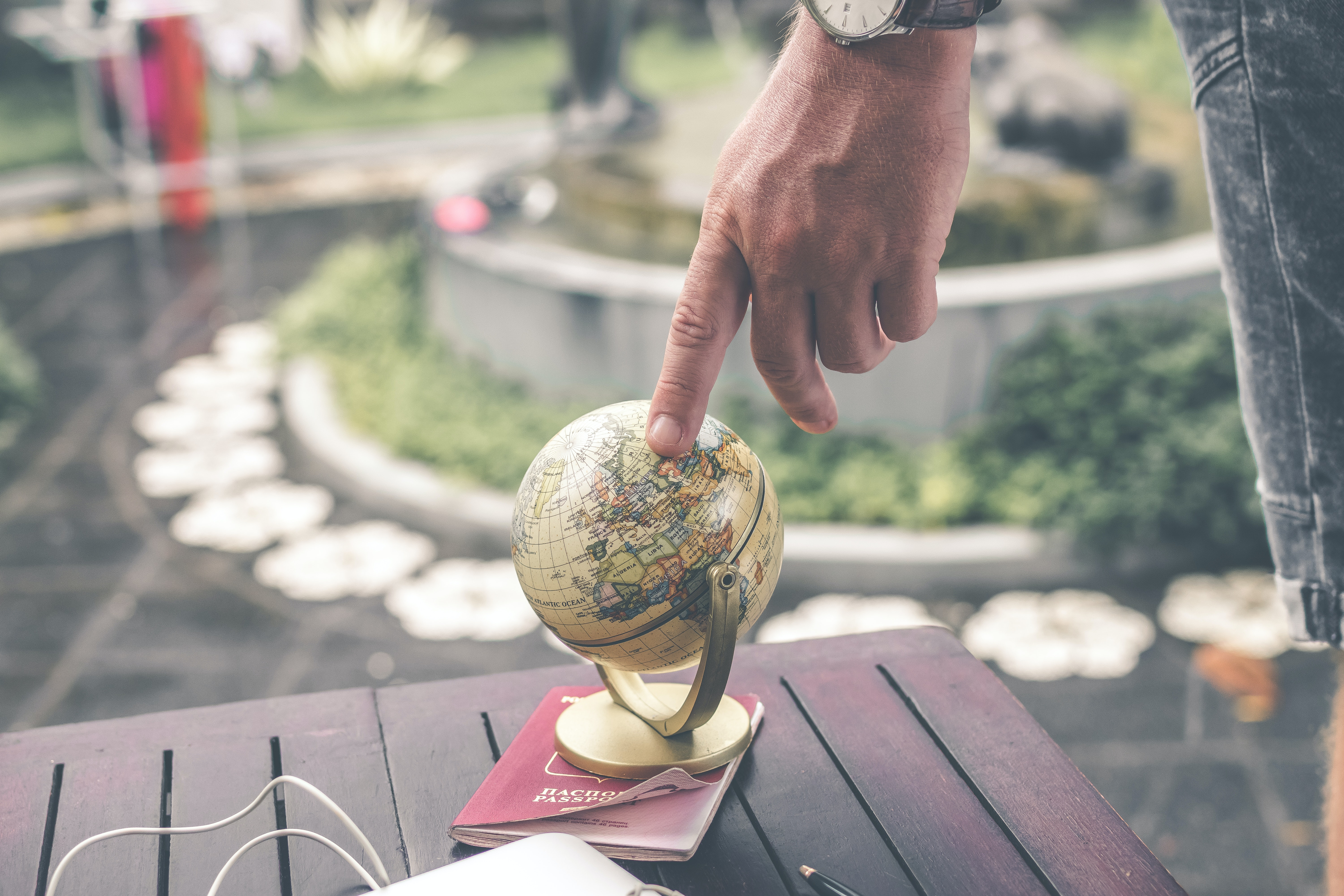 Person's finger touching the globe thinking of studying abroad