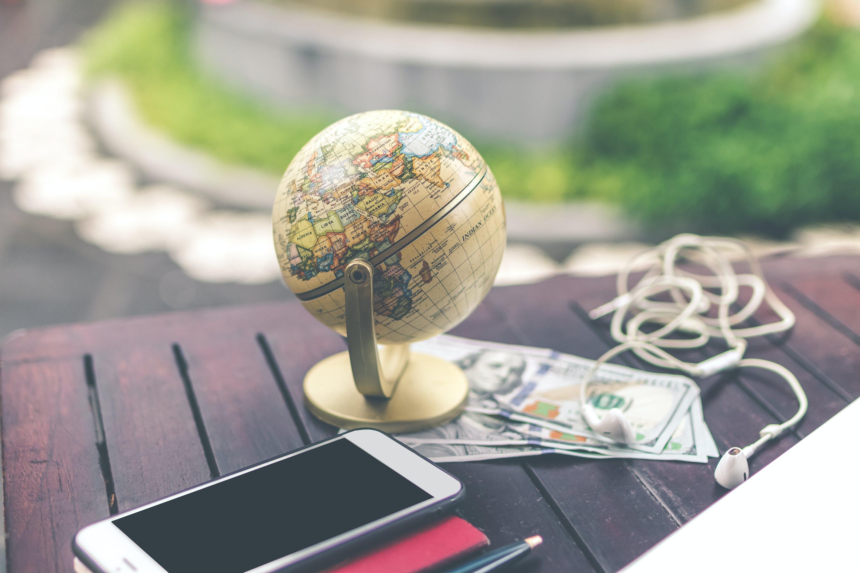 Desk globe on table near smartphone