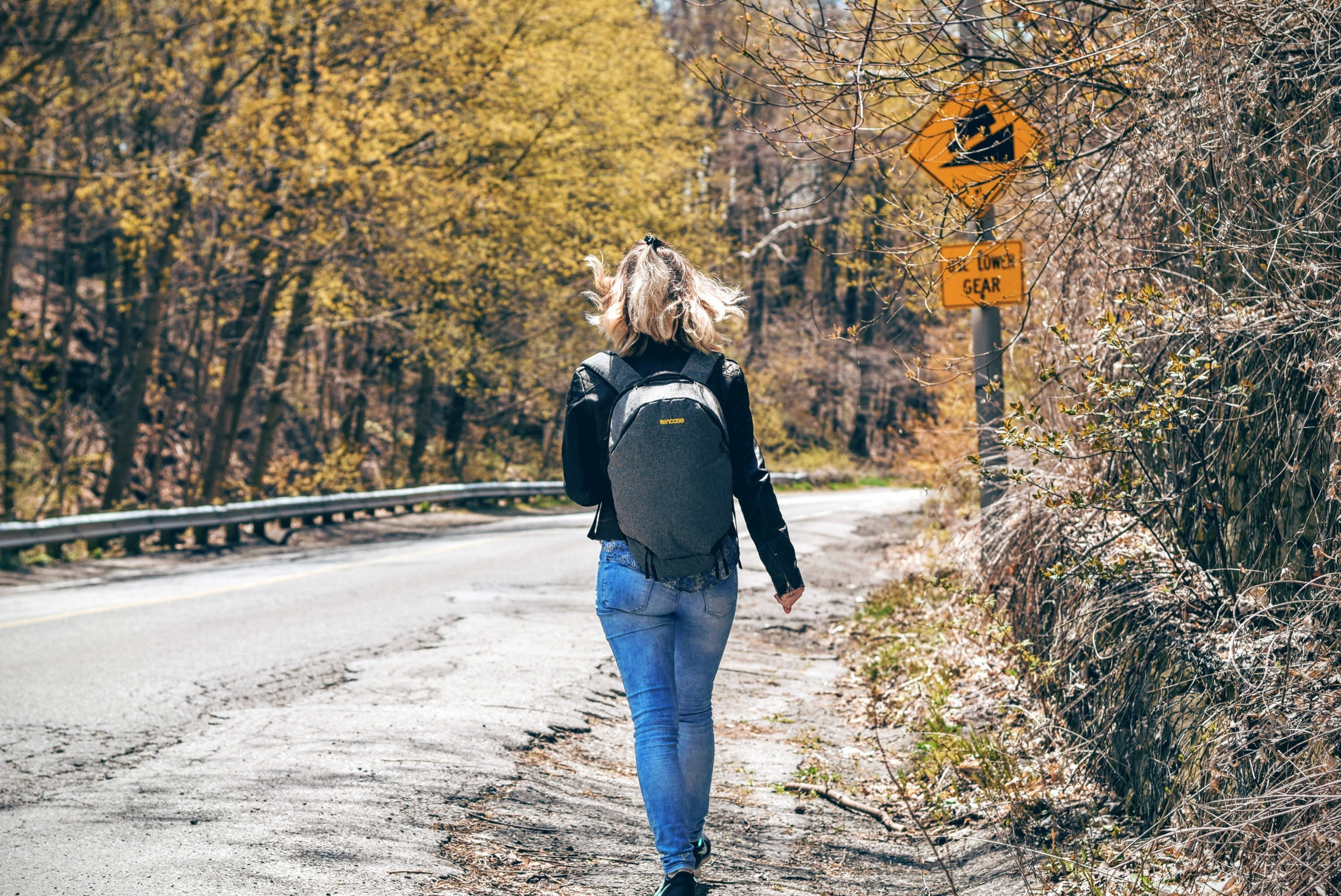 Woman in Blue Denim Fitted Jeans and Wearing Grey Backpack Walking on Gray Asphalt Road Near Road Signage and Trees at Daytime