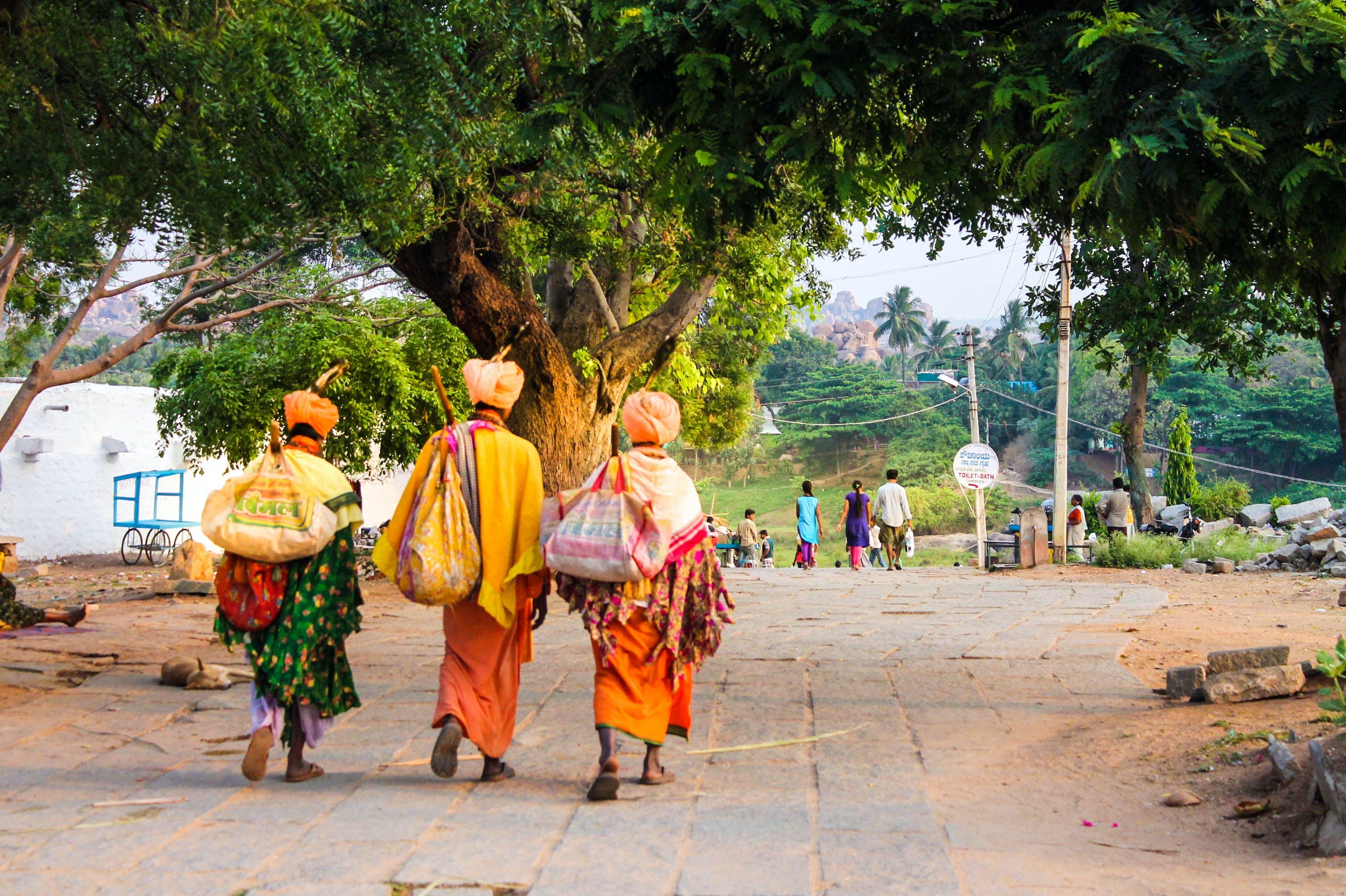 Three Person Walking on Concrete Road