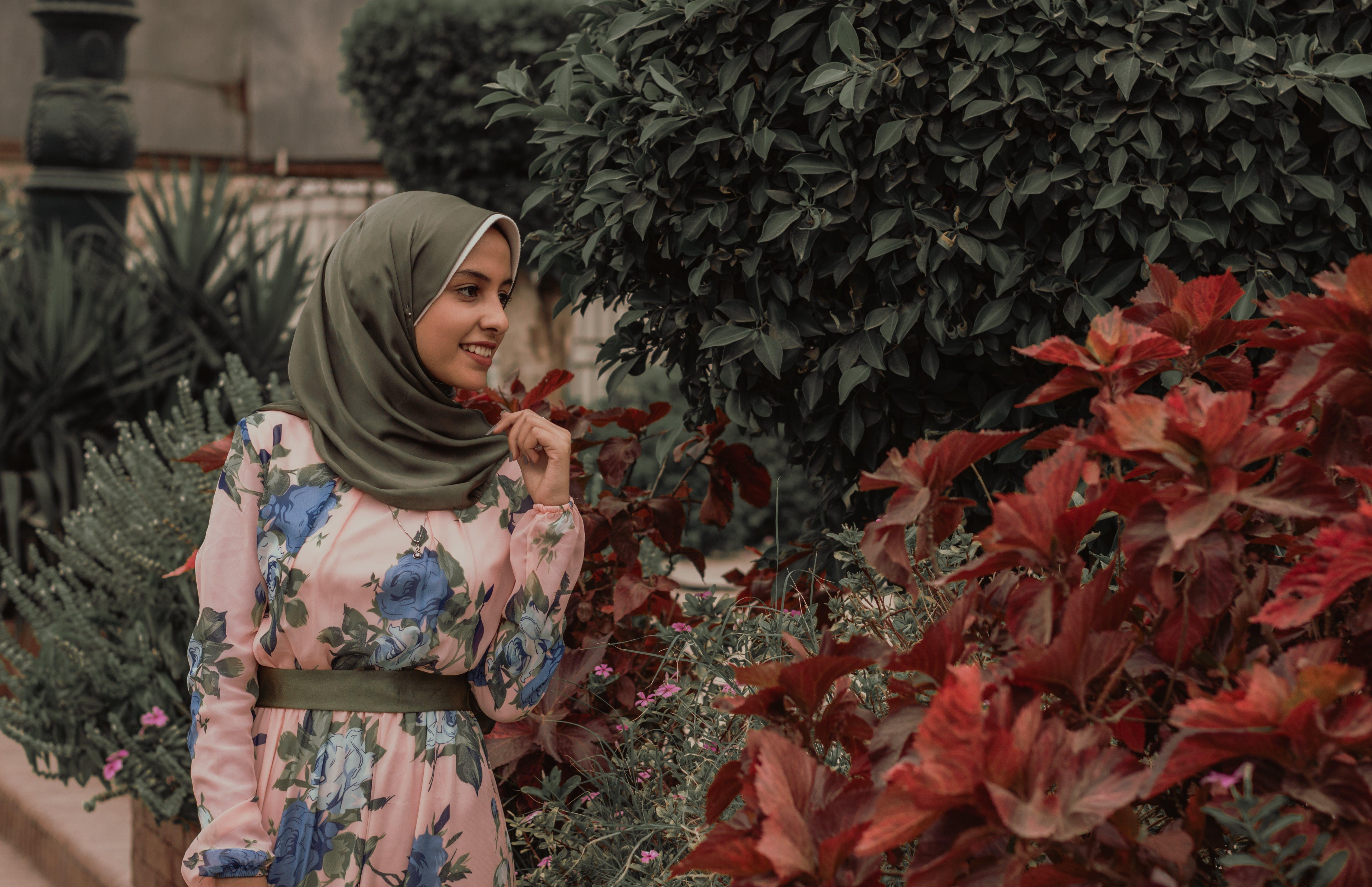Woman Beside Red Petal Flowers