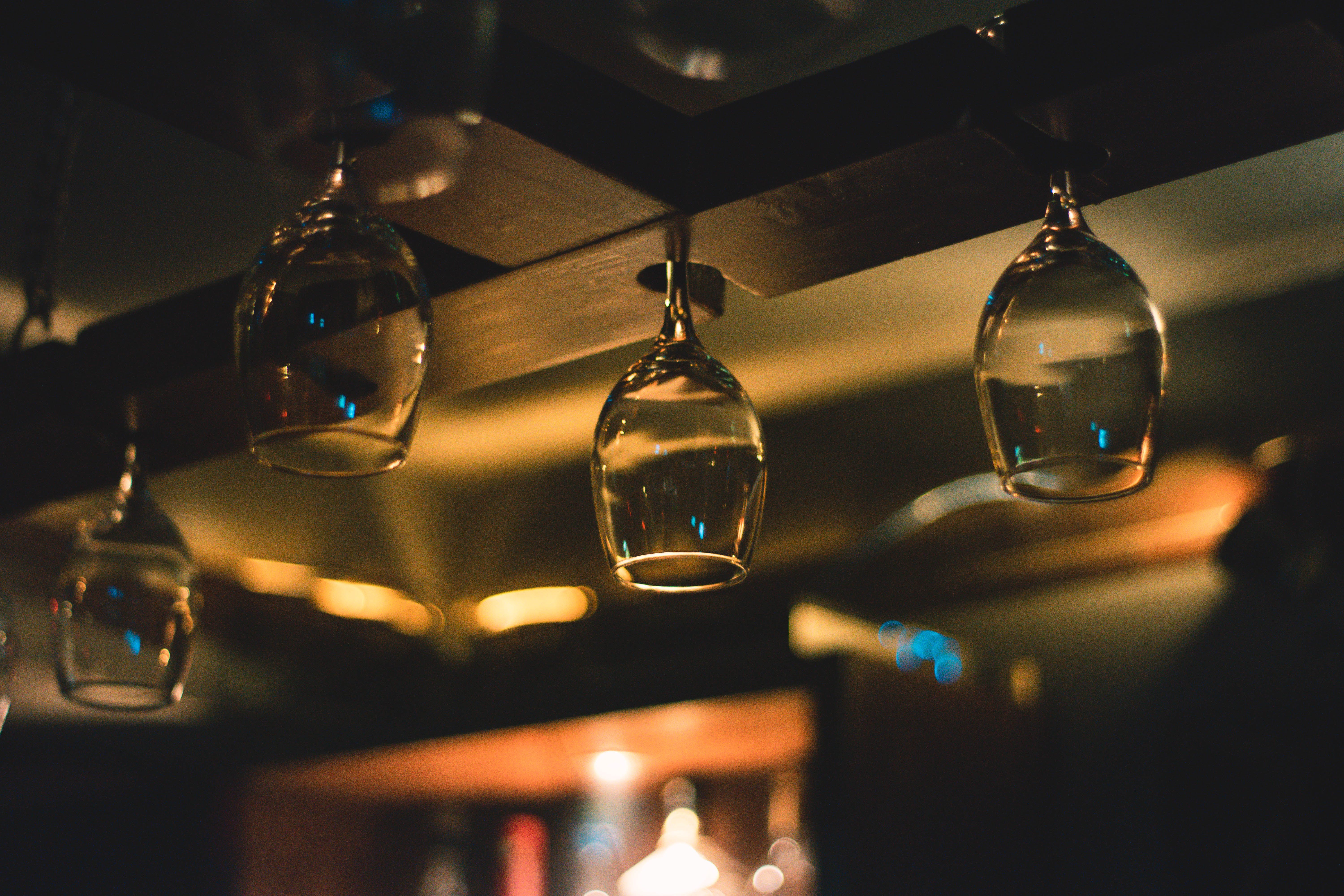 Selective Focus Photography of Wine Glass Hanging on Black Wooden Rack