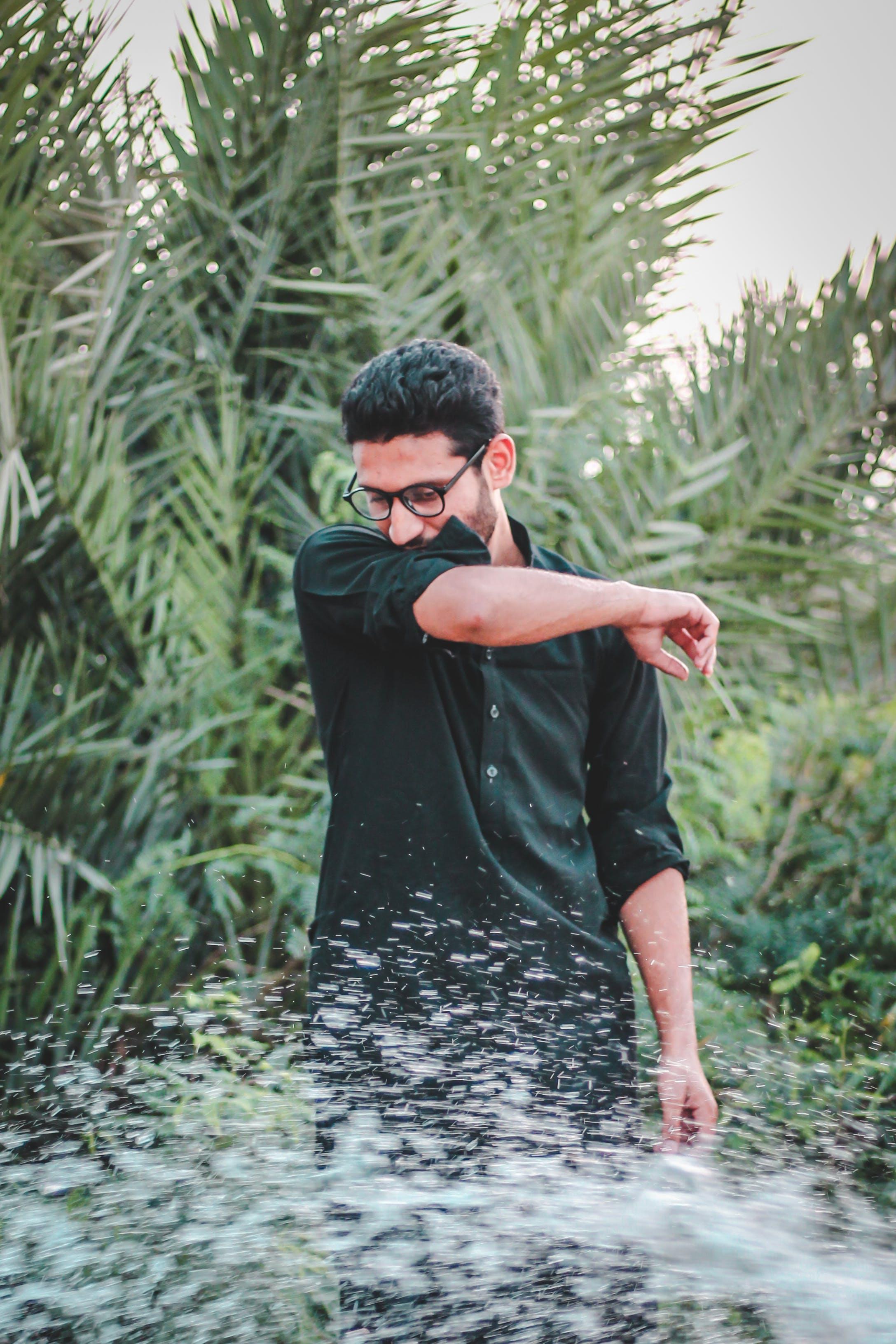 Man in Green Dress Shirt Near Palm Trees