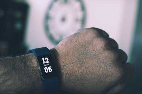 Blue Fitbit Charge Displaying 12:05 May 9