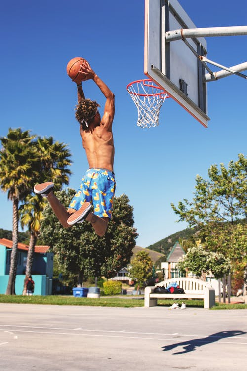 Man Wearing Blue and Yellow Shorts Playing Basketball