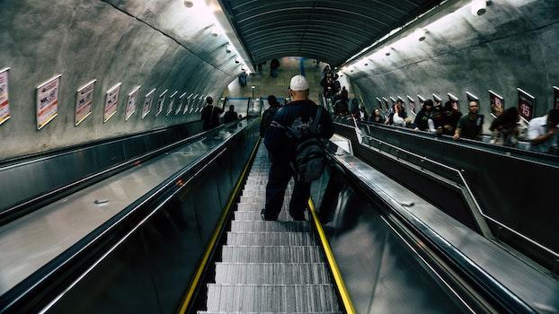 Man in Black Leather Jacket on Escalator