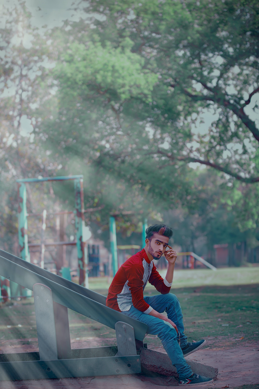Man Wearing Red Long-sleeved Shirt Sitting On Slide