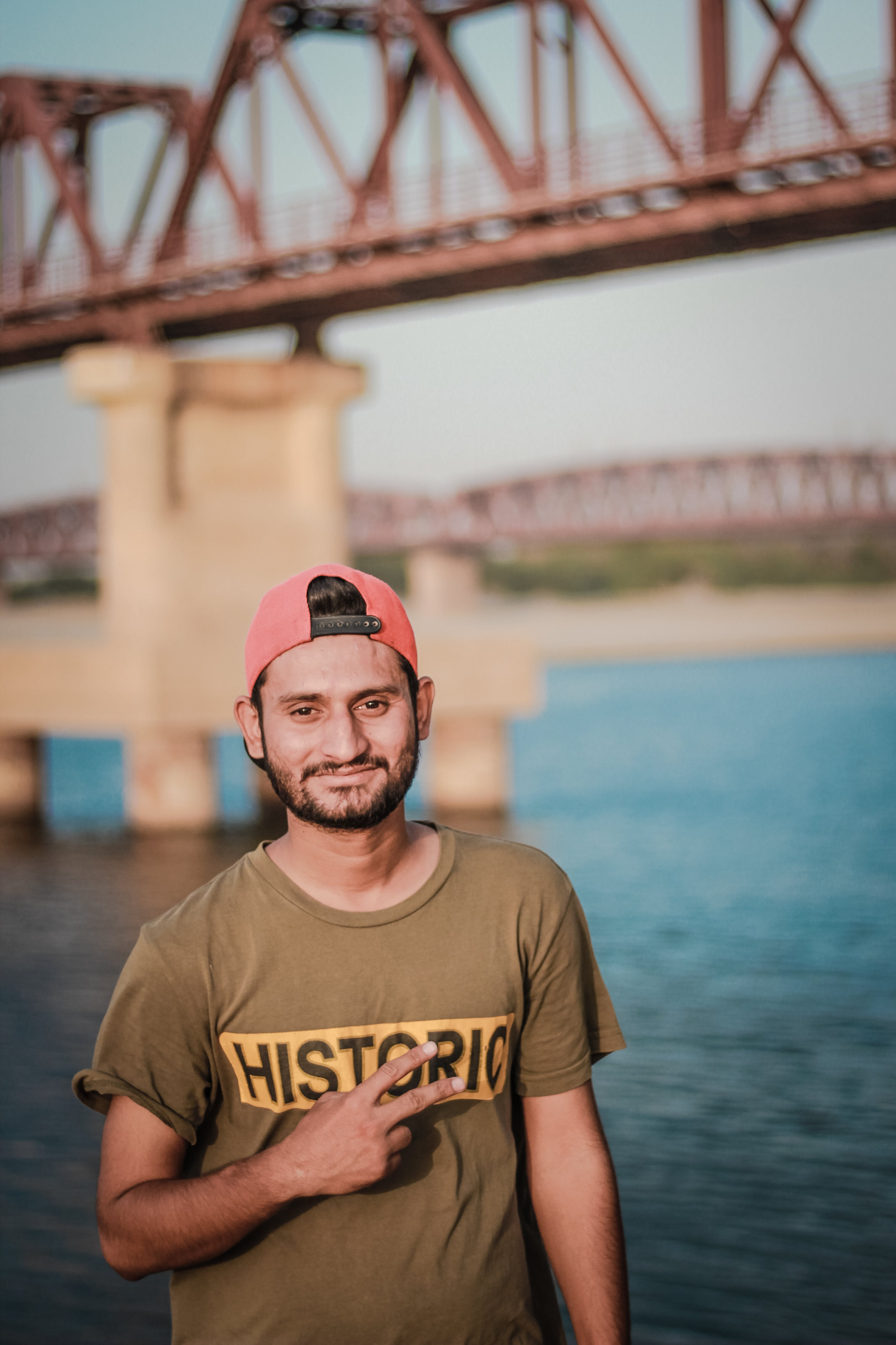 Man Wearing Gray Historic-printed T-shirt and Red Snapback Cap Taking Photo Beside Body of Water