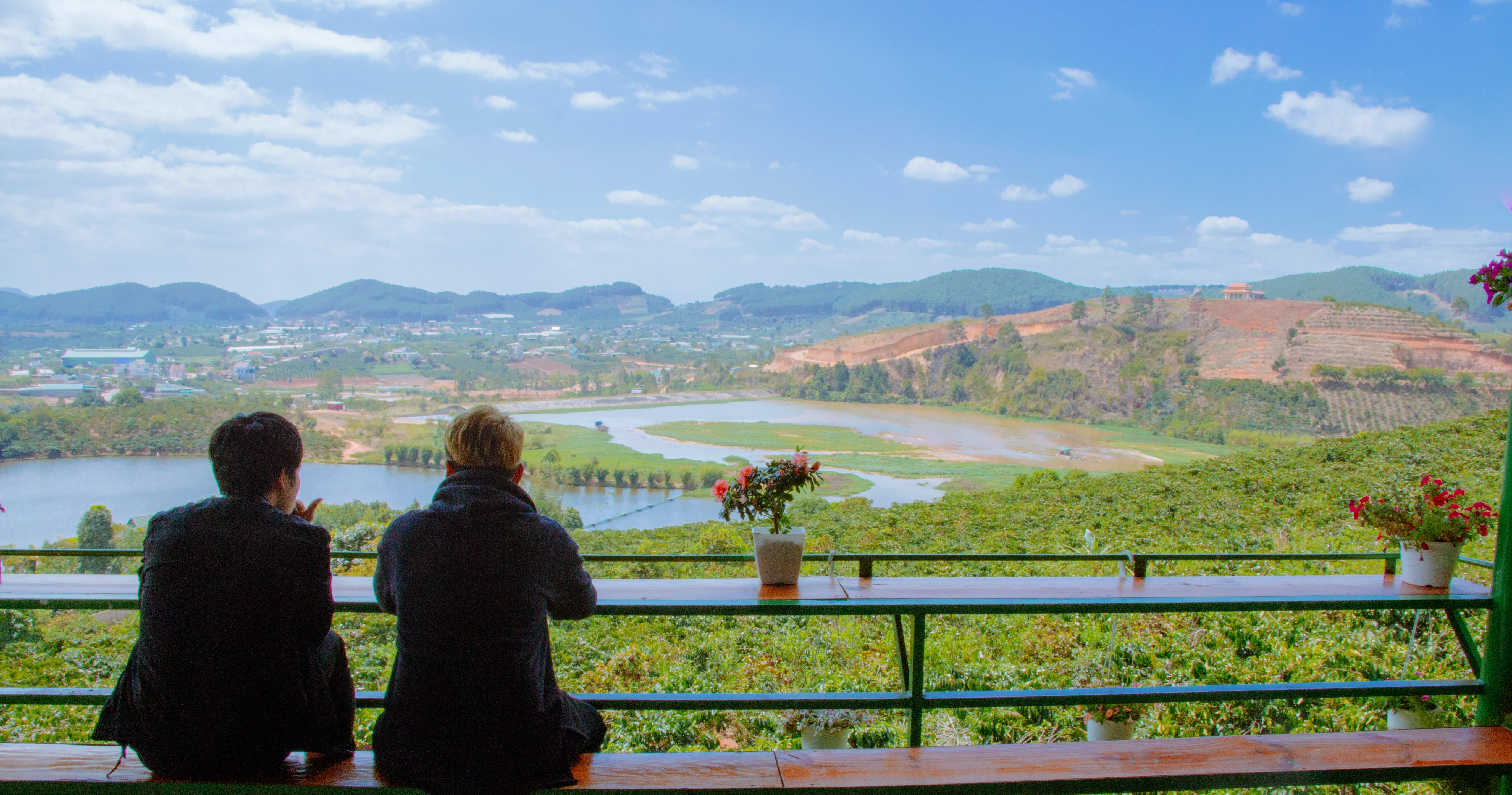 Two Men Sitting On Table Facing Lake