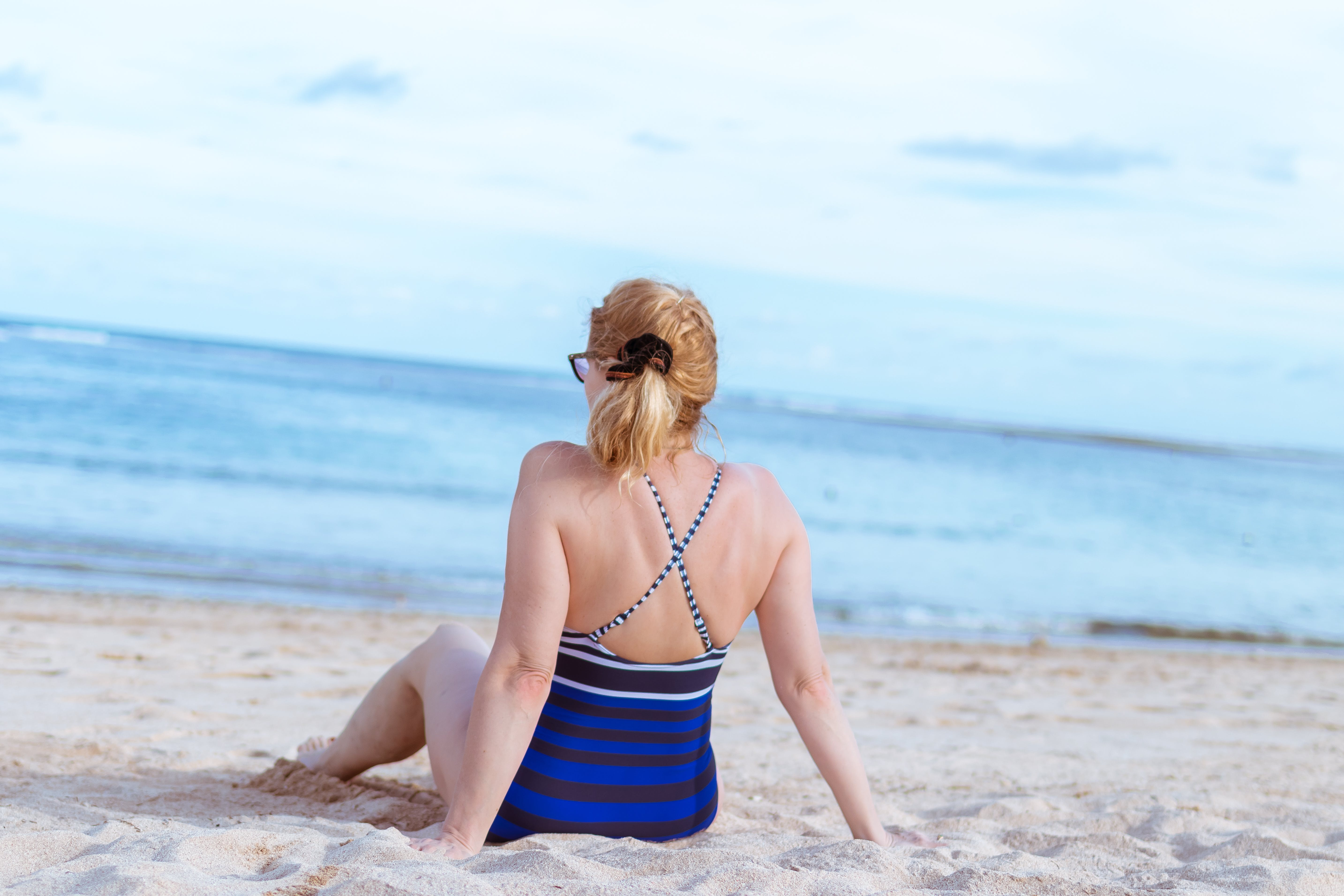 Woman Sits on White Sand Beach
