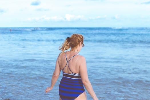 Woman Wearing Blue Monokini Standing Beside Body Of Water Under Blue Sky