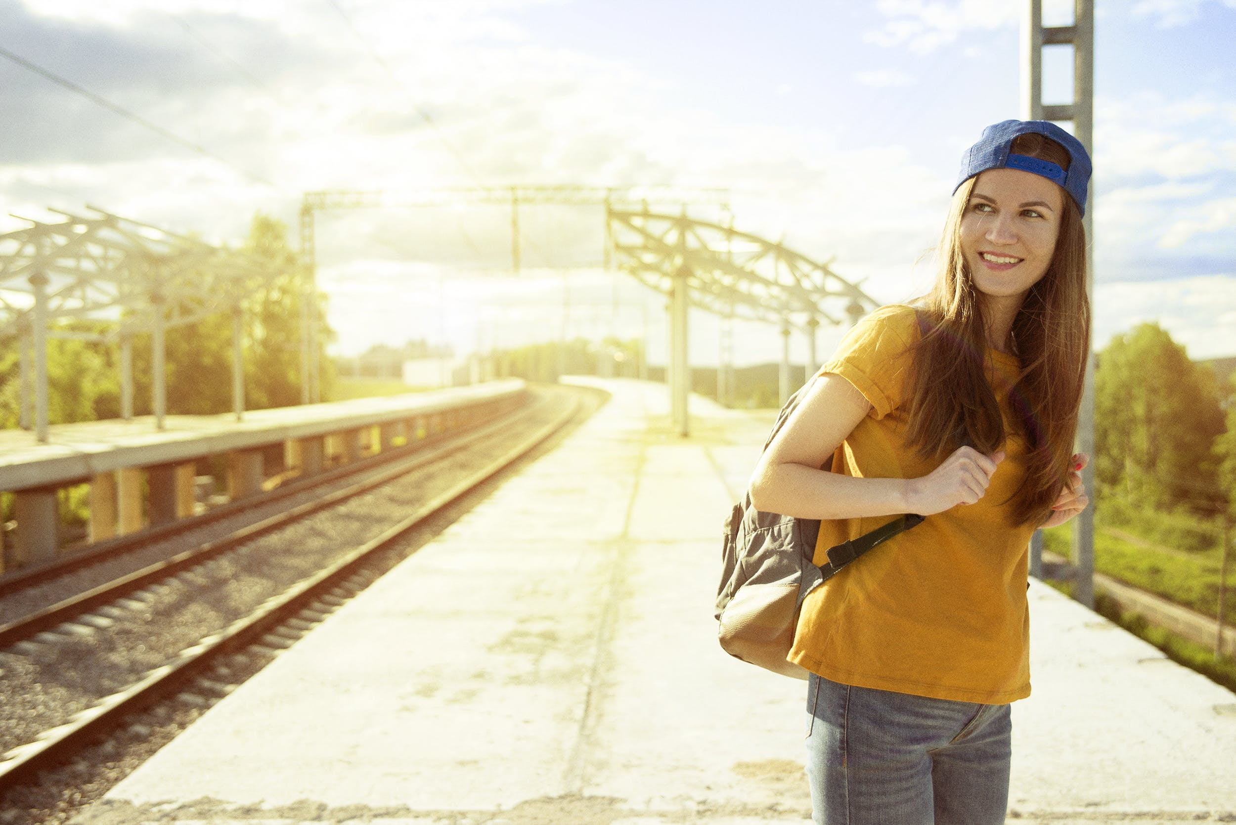 Smiling Woman in Orange T Shirt and Blue Snap Back Cap Carrying Backpack