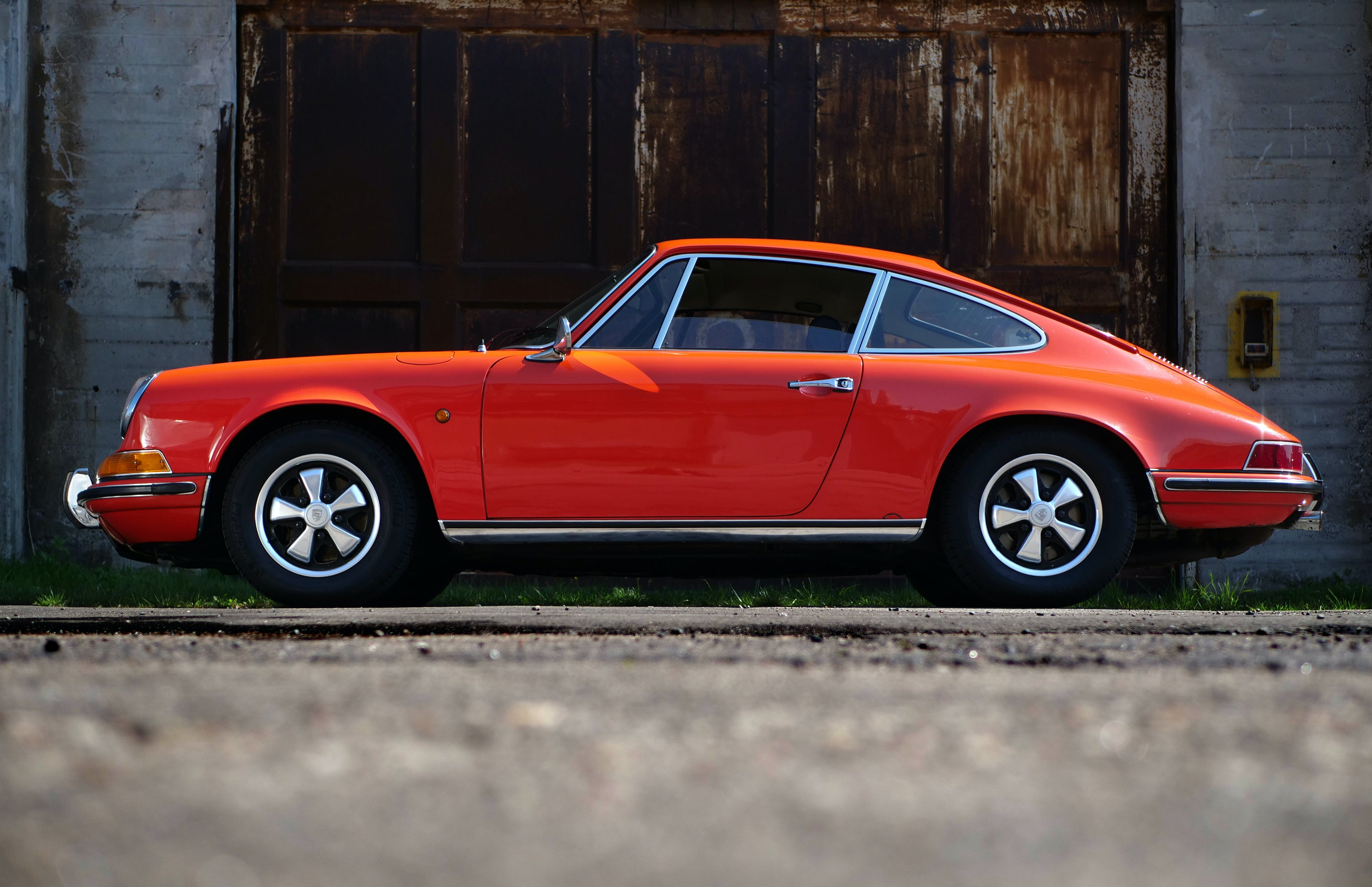 Orange Fastback Car Near Wall
