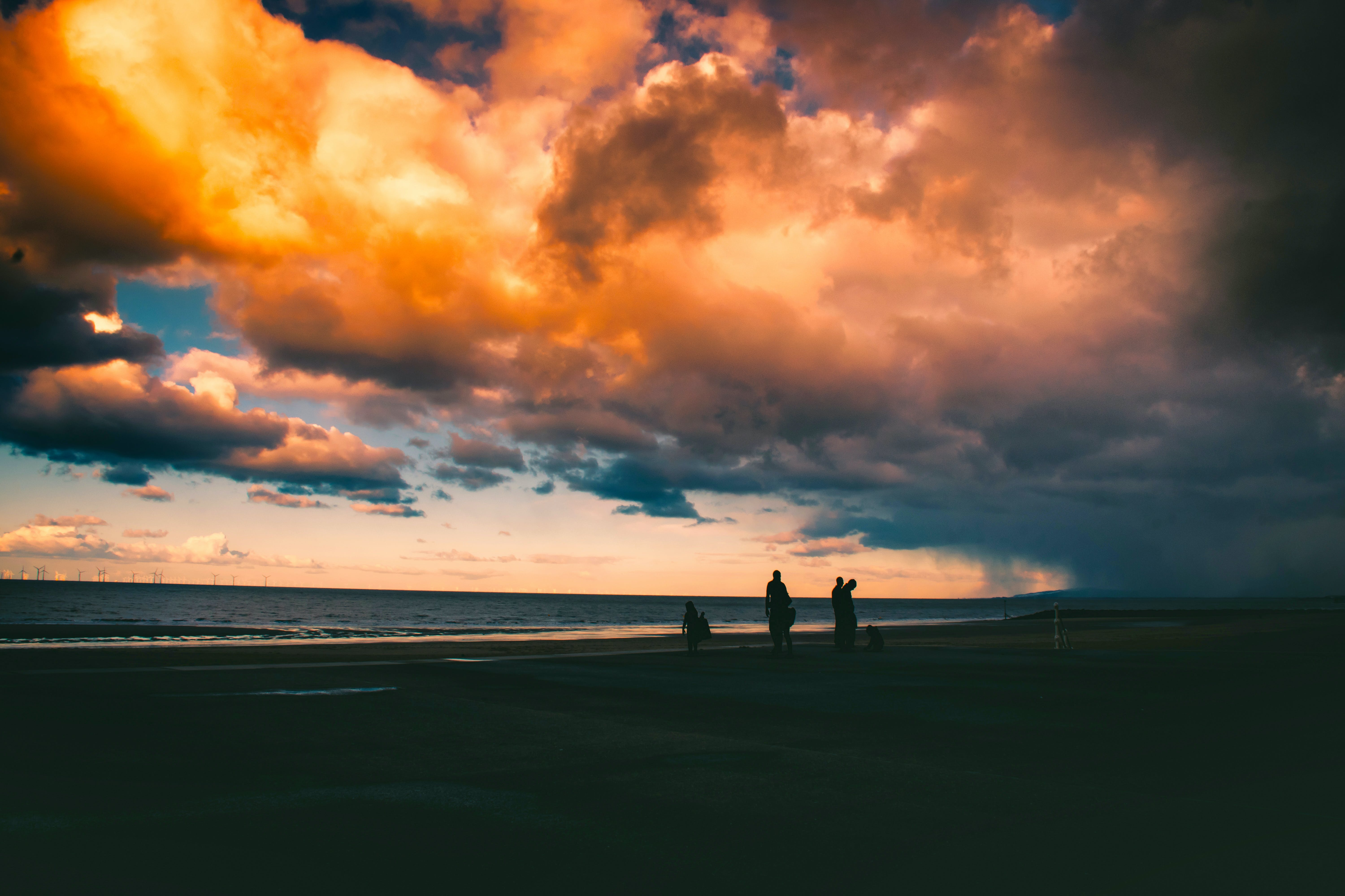Silhouette Of People On Shore Under Cloudy Sky
