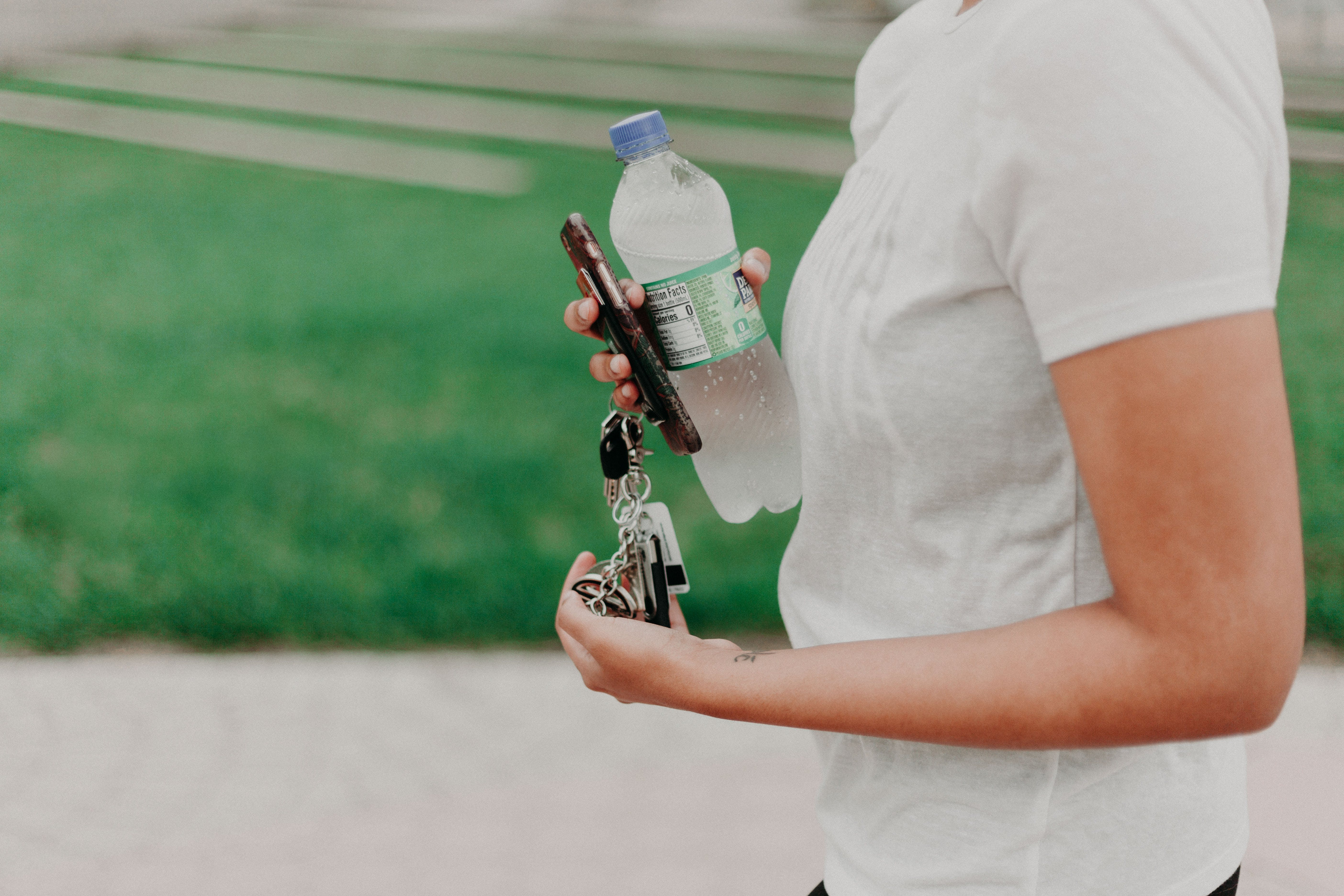 Person Holding Key, Smartphone, And Plastic Bottle