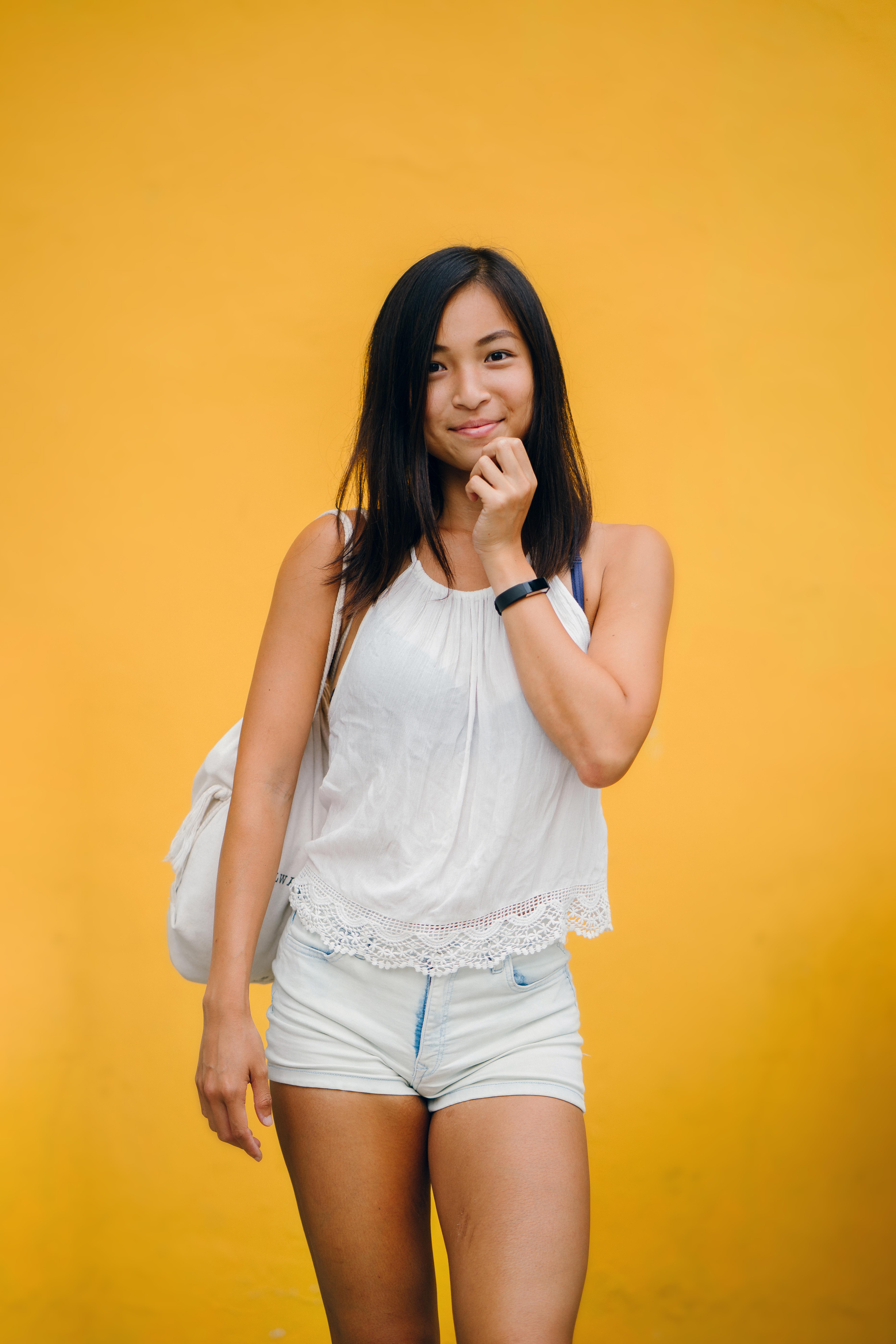 Woman Wearing White Sleeveless Shirt And White Denim Shorts