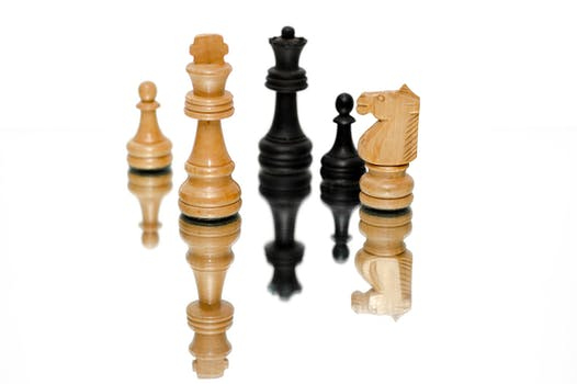 Photo of Black and Beige Wooden Chess Pieces With White Background