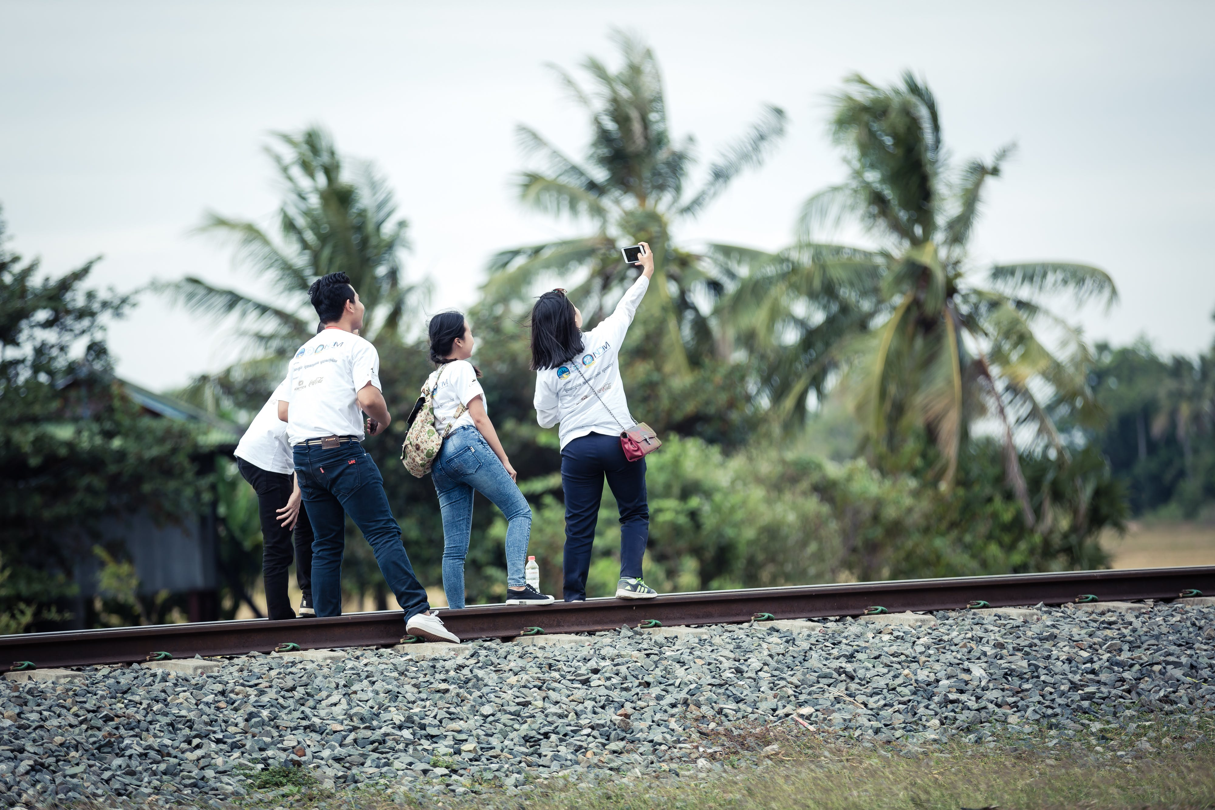 Person Taking a Selfie With Three Persons on Train Railway