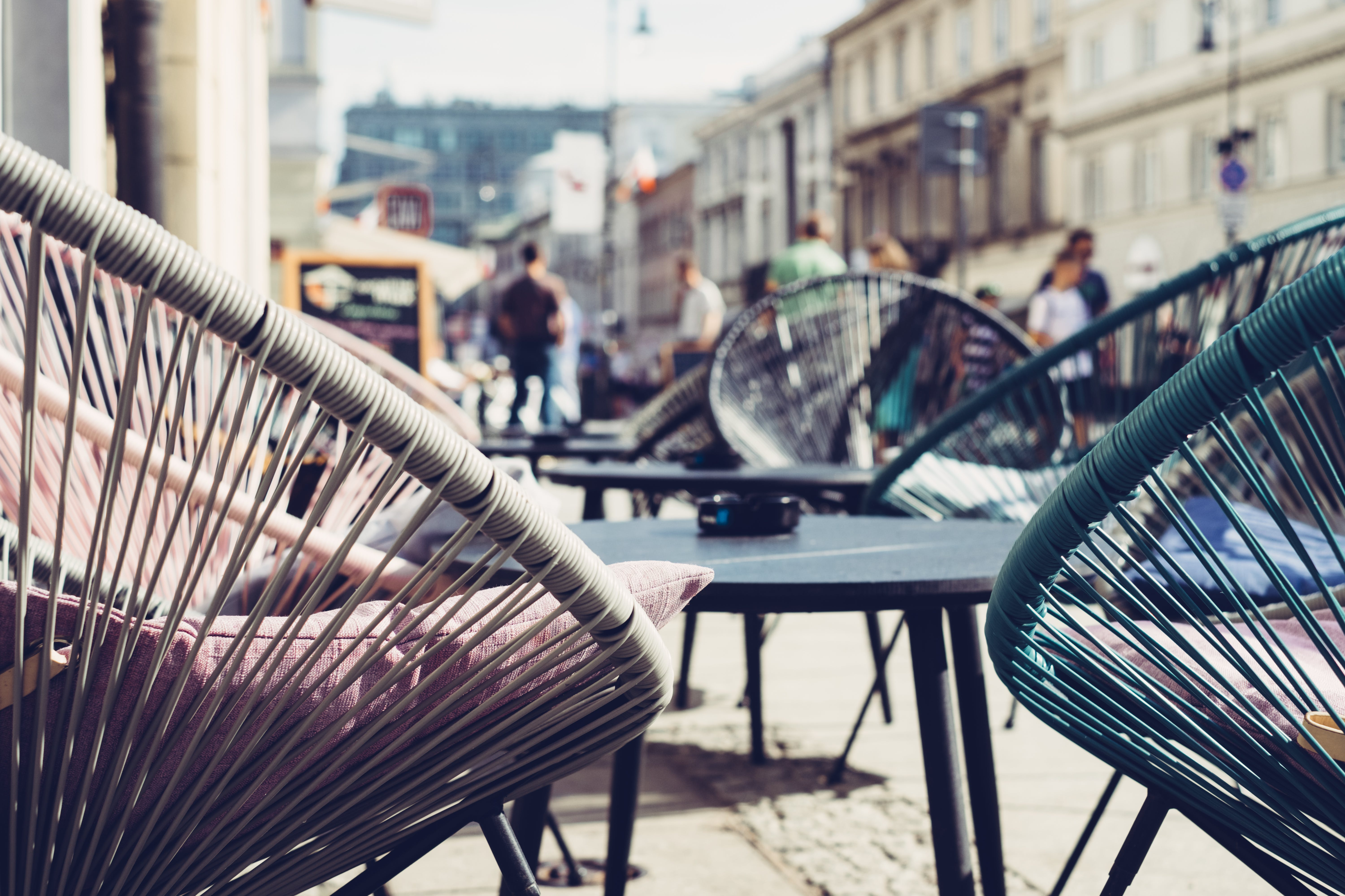 Selective Focus Photography of Patio Set Near Walking People