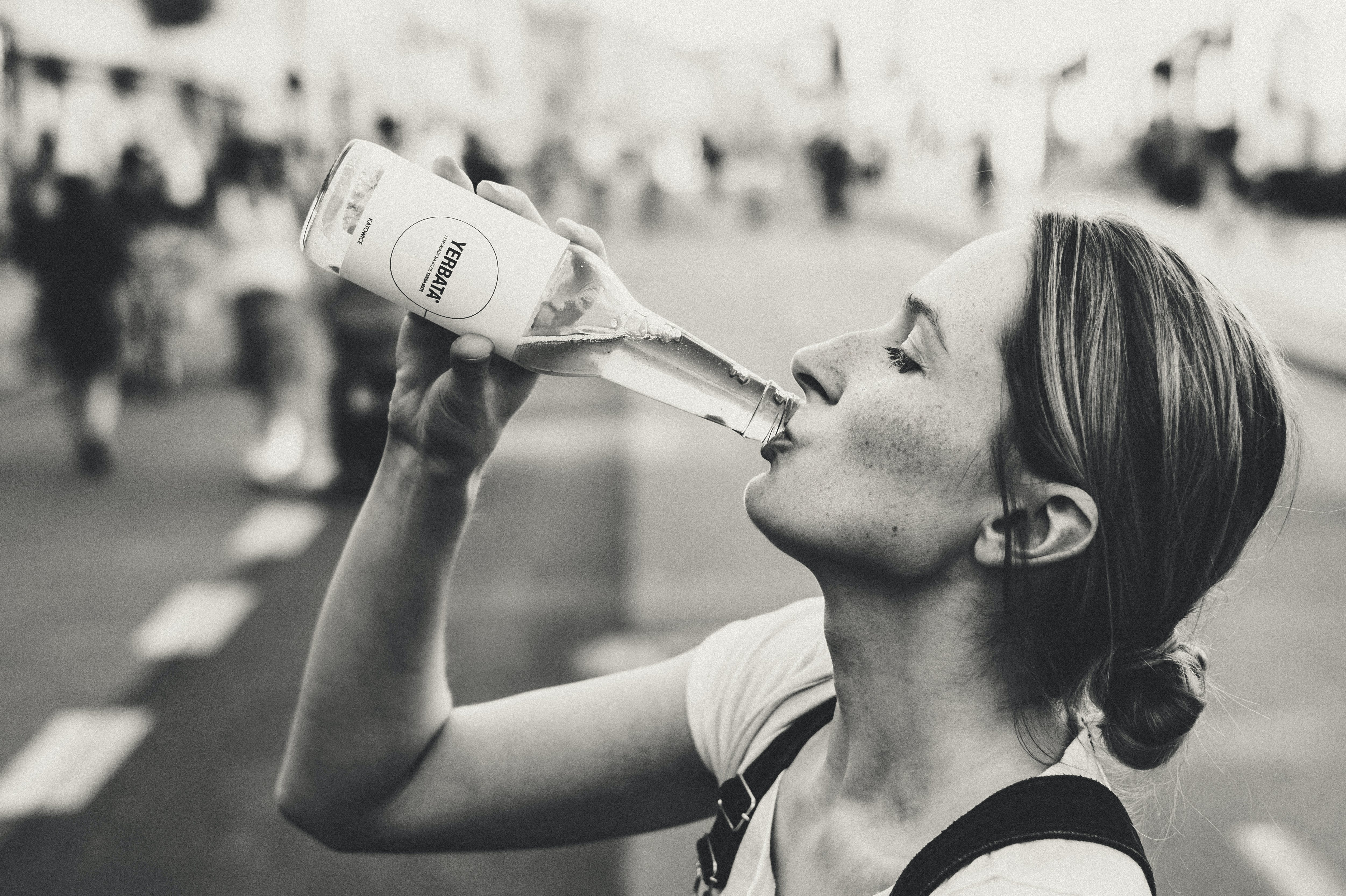 Woman Holding Glass Bottle in Grayscale Photo