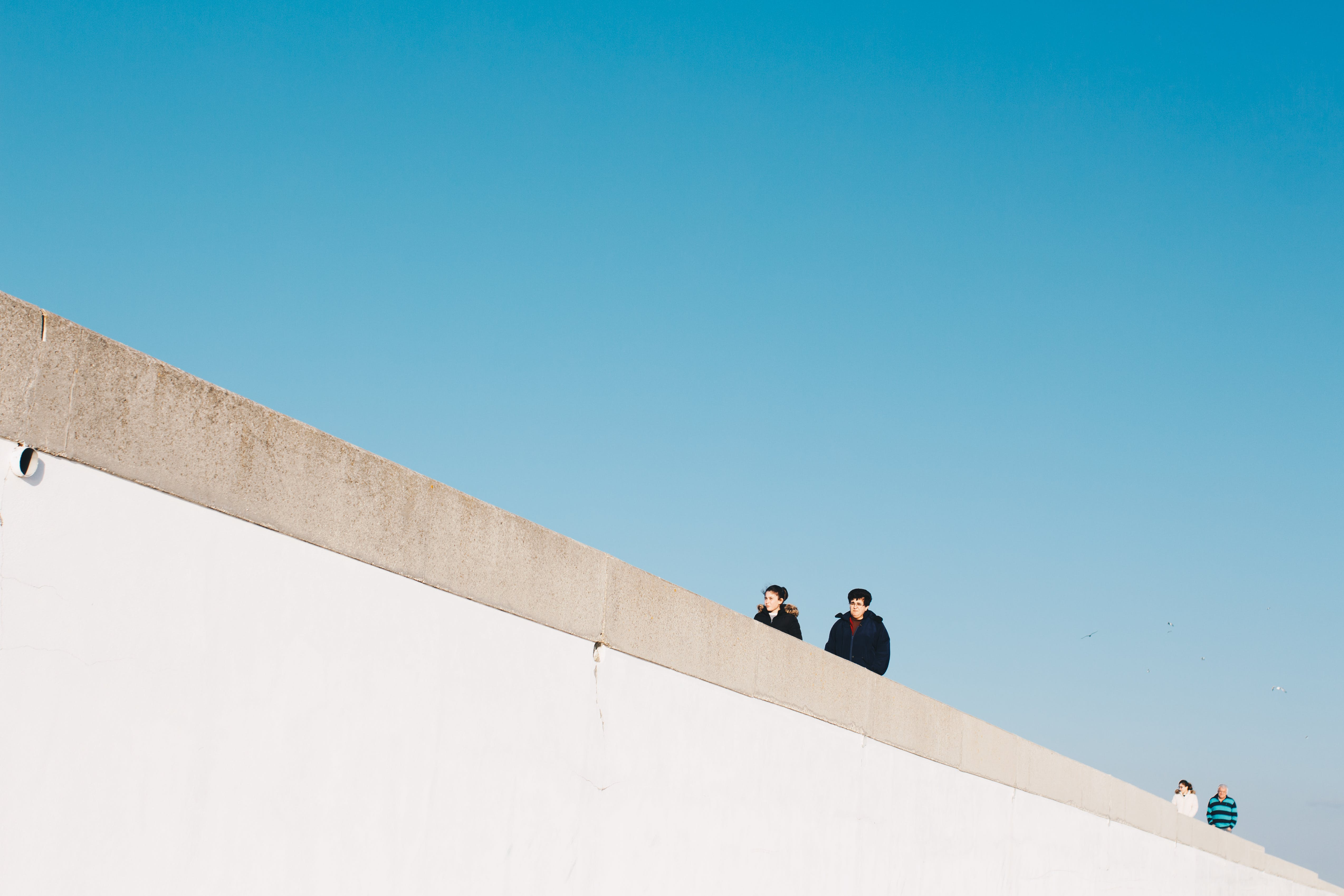 Four Person Wearing Jacket Under White Cloud Blue Skies
