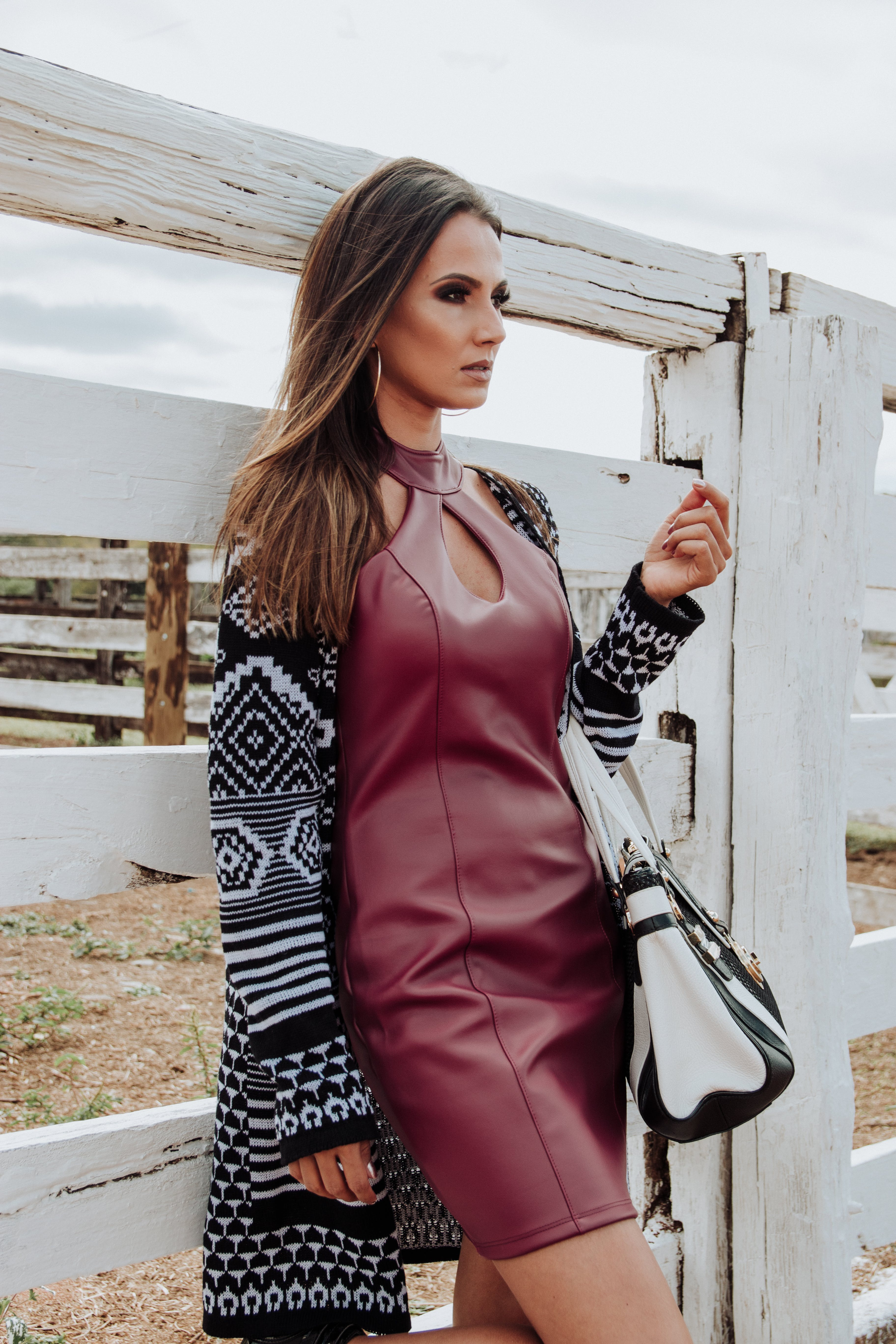 Woman Wearing Maroon Leather Dress and Cardigan Leaning on White Plank Wall