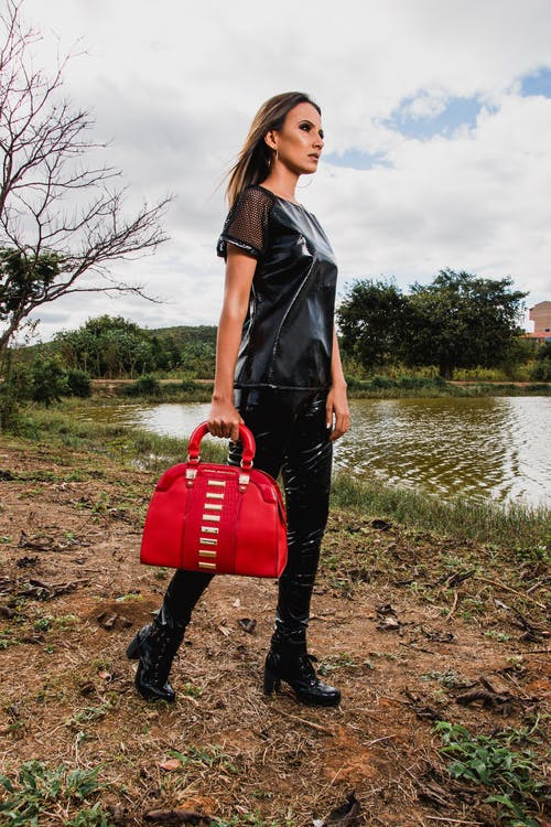 Woman Wearing Black Suit Holding Red Leather Duffel Bag during Day