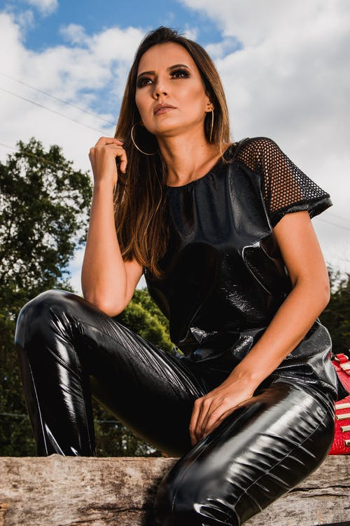 Woman in Black Leather Pants Sitting on Log