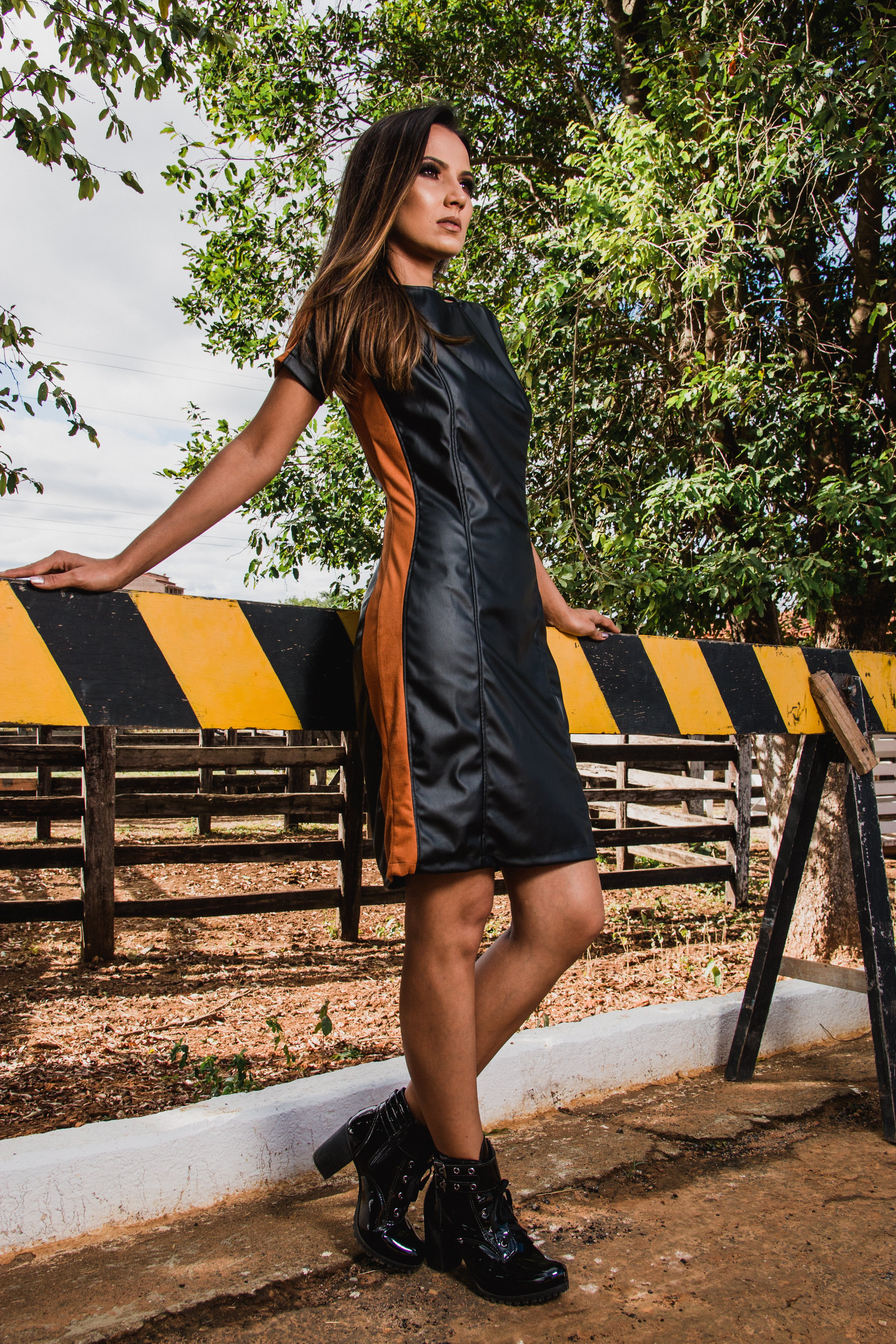 Woman Wearing Black and Brown Leather Midi Dress and Black Chunky Heeled Boots