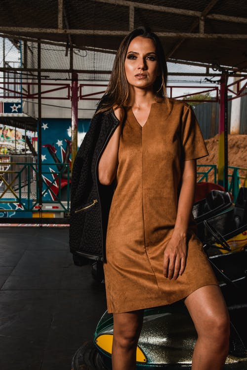 Photo Of Woman In Brown Mini Dress Holding Black Jacket