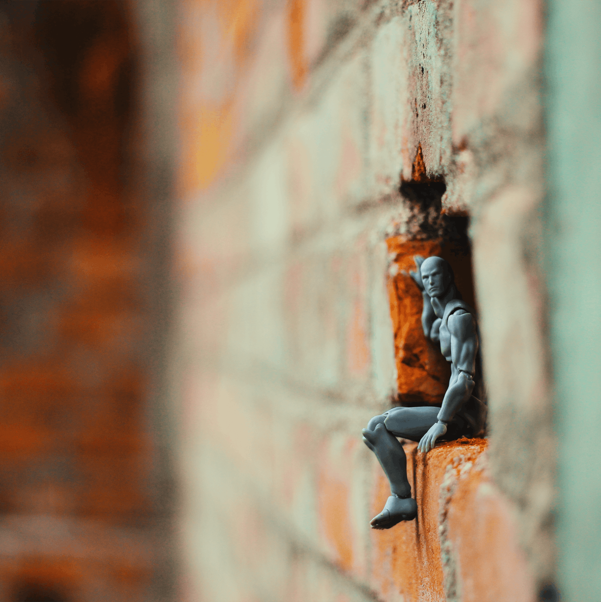 Action Figure on a Hole of Brick Wall