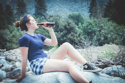 Woman In Blue Shirt Sitting On Rock Drinking Coca-cola