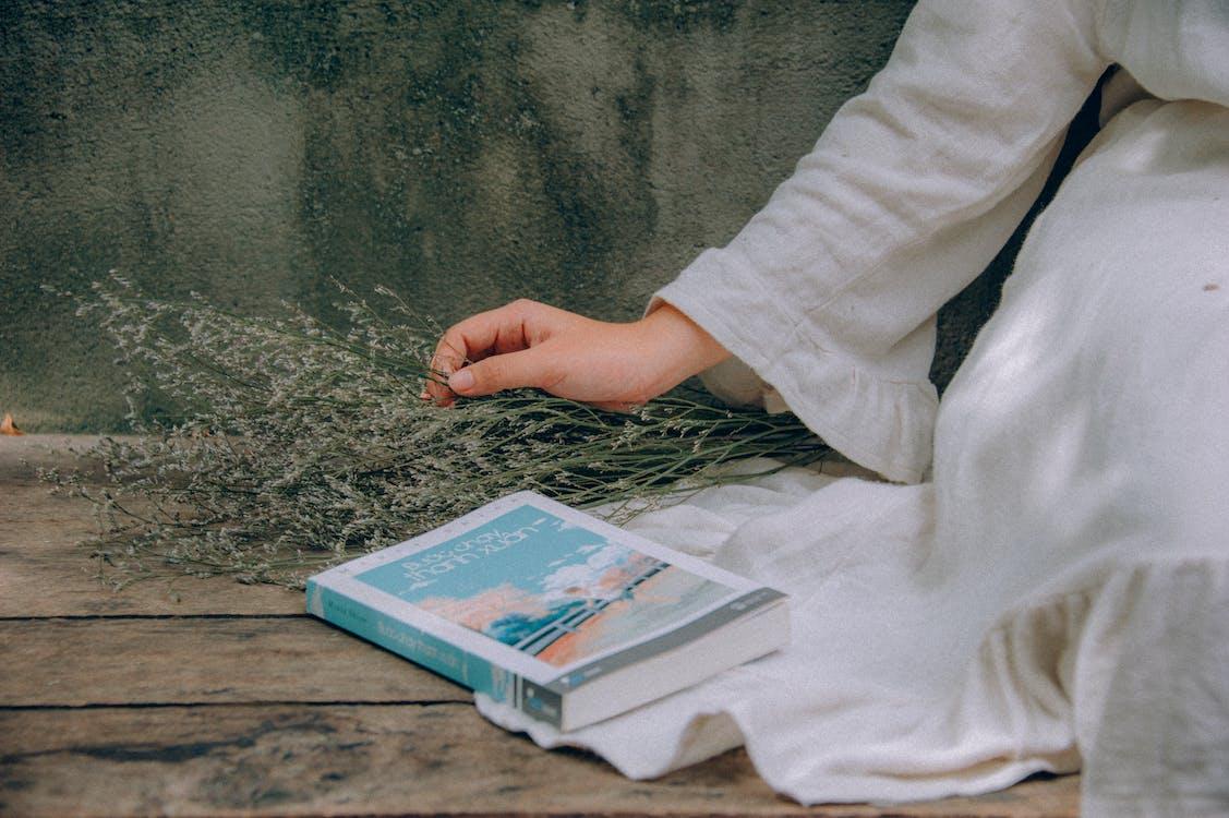 白いドレスを着ている女性の横にある青と白の本