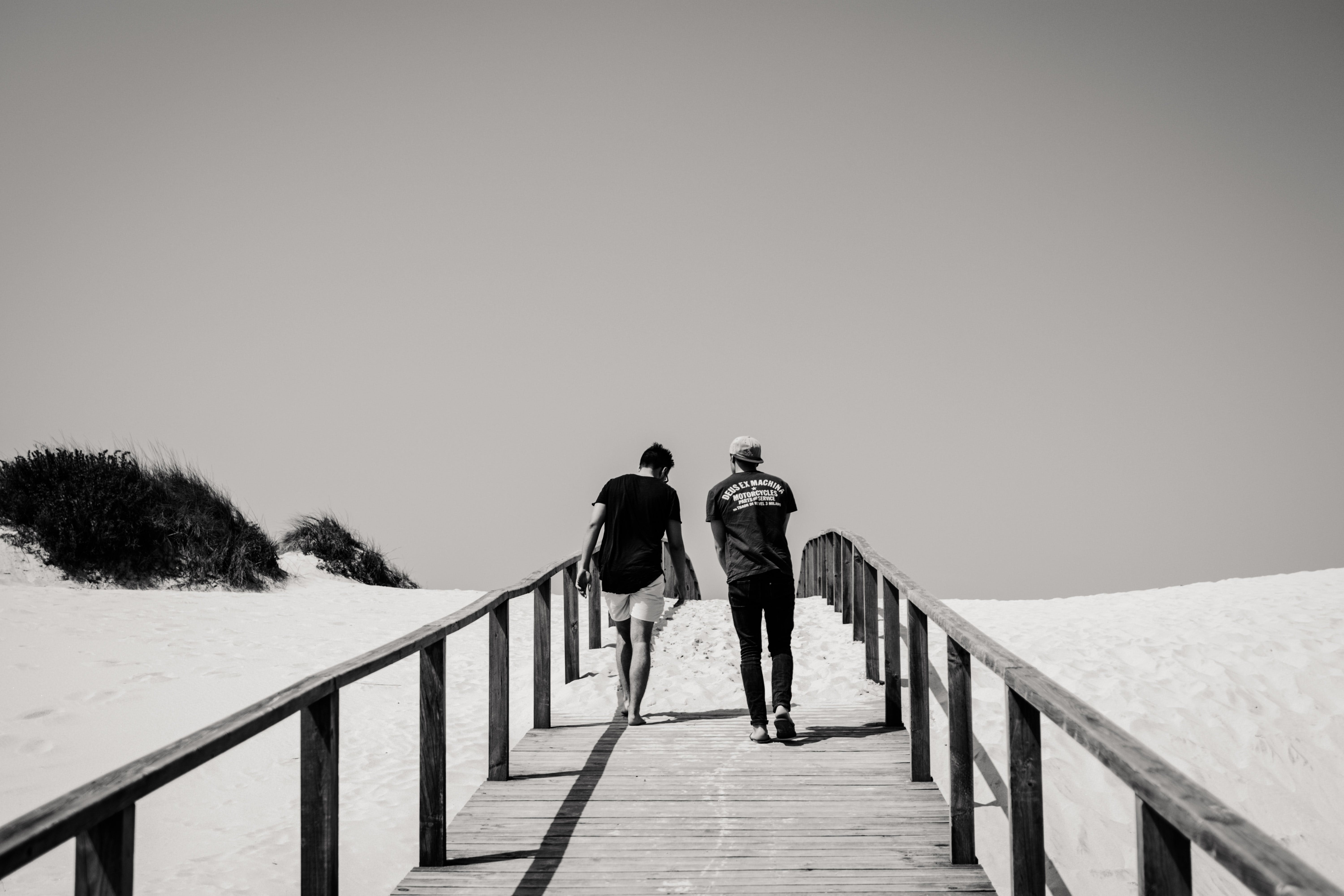 Grayscale Photography of Man and Woman Crossing Bridge
