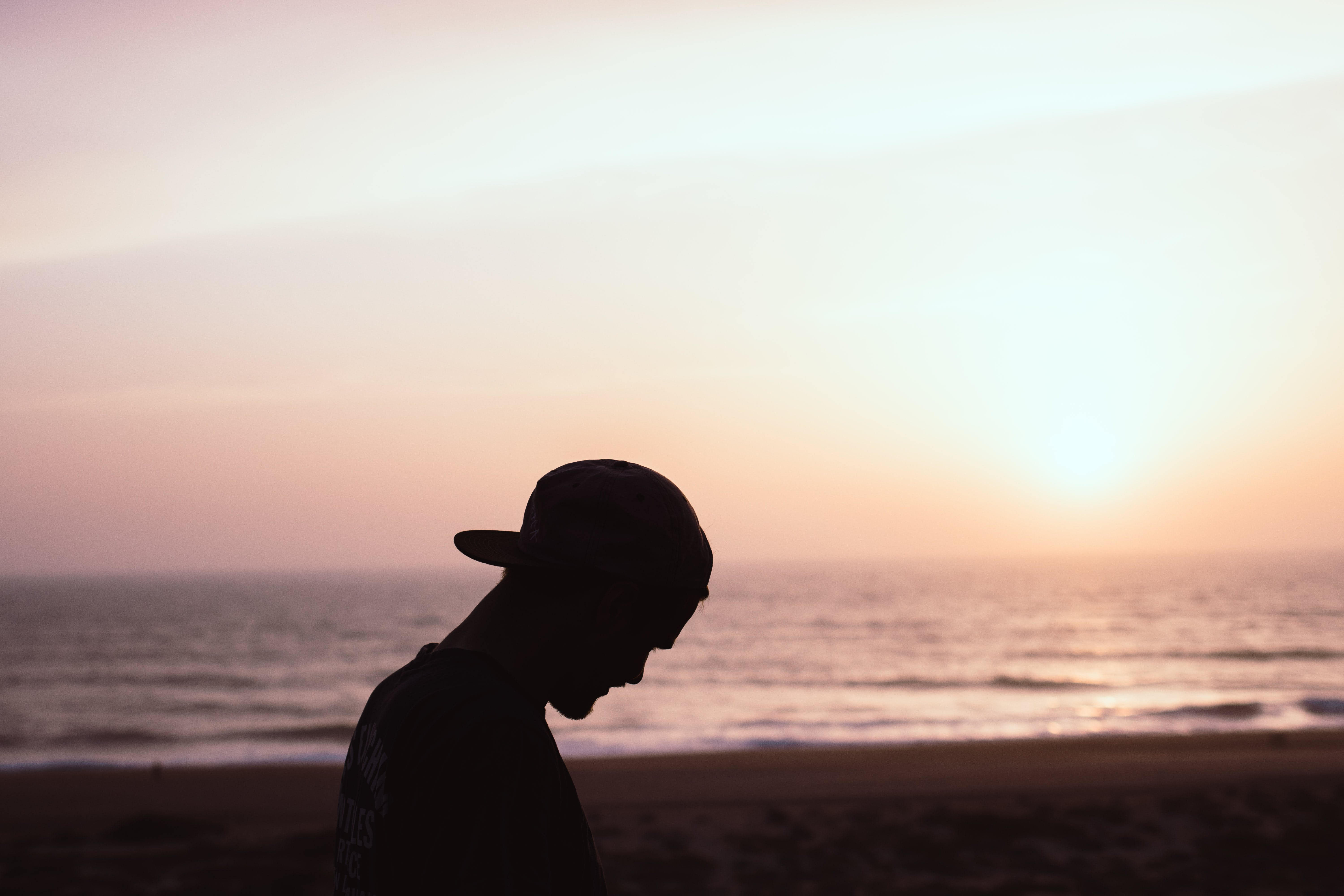 Silhouette of Man Wearing Cap at the Beach