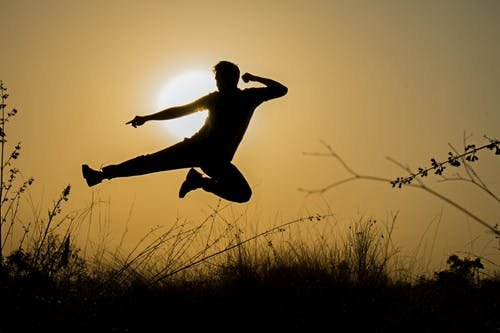Silhouette of Man Doing Kick Jump during Sunset