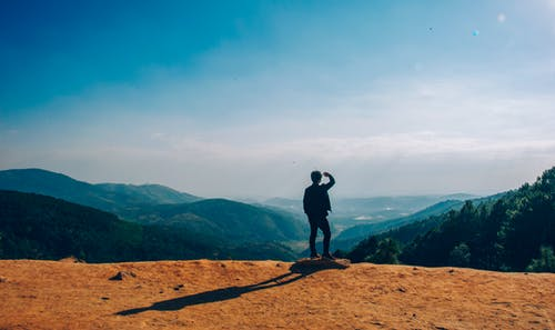 Silhouette of Man Standing on Mountain Cliff