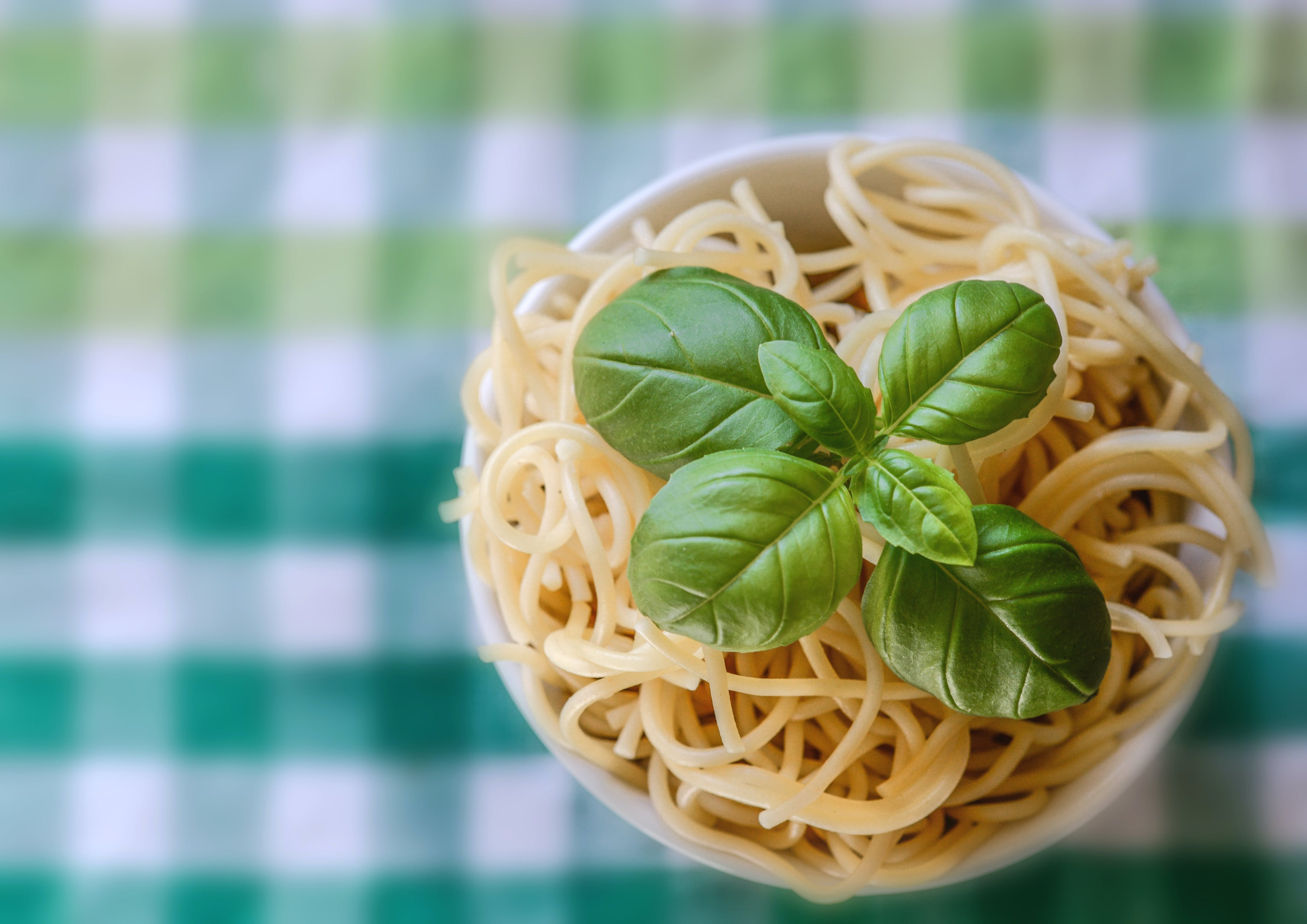 Selective Focus Photo of Noddles With Green Leaf Toppings