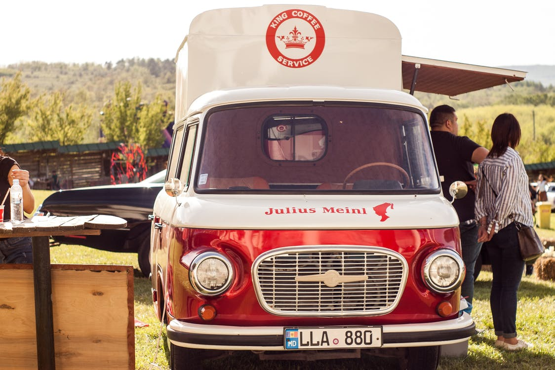 People Standing Beside of Red and White Van