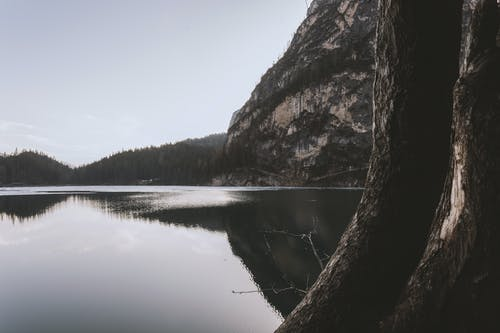 Landscape Photography of Lake Beside Cliff at Daytime