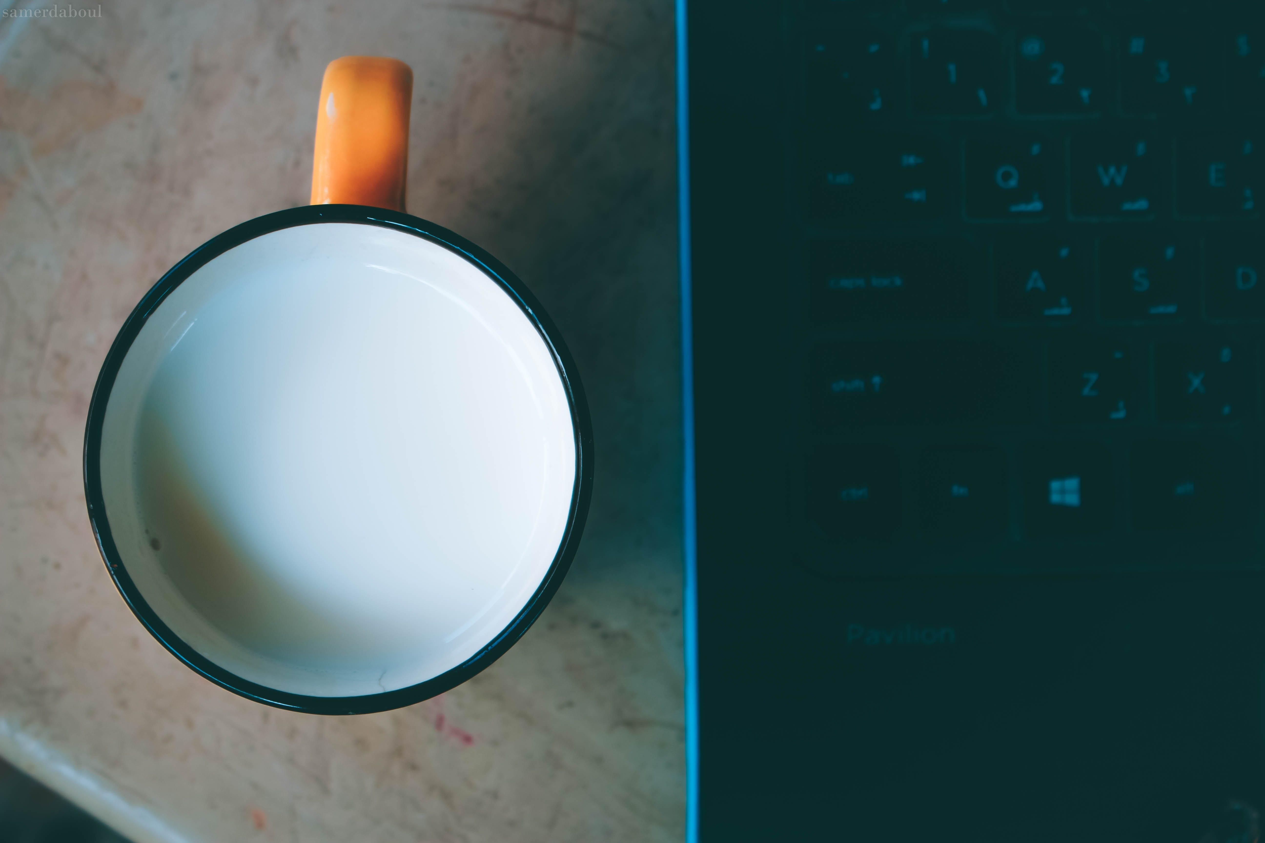 Orange and Black Ceramic Mug With Milk Beside Black Laptop