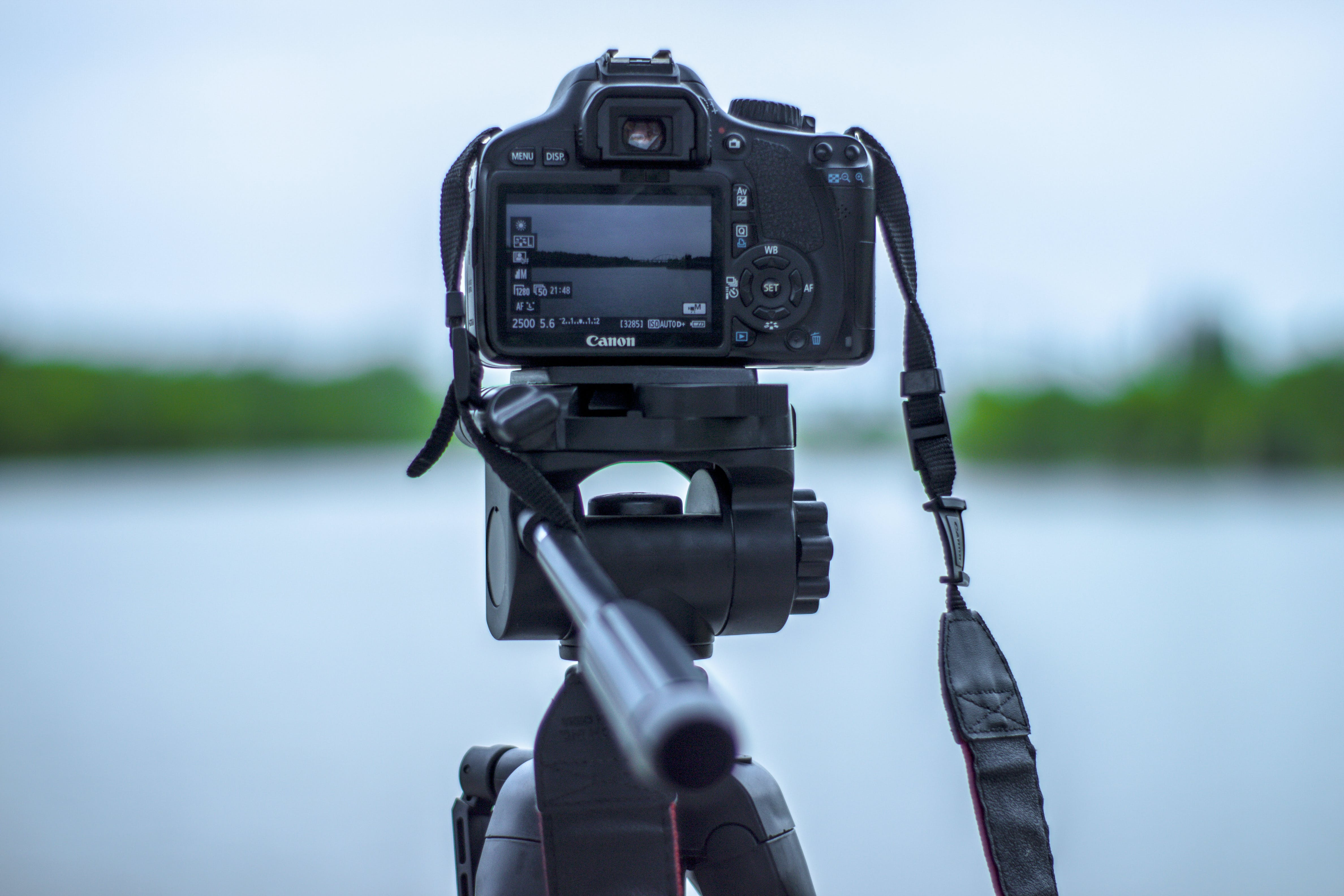Selective Focus Photo of Black Canon Camera on Tripod Stand in Front of Body of Water Photo
