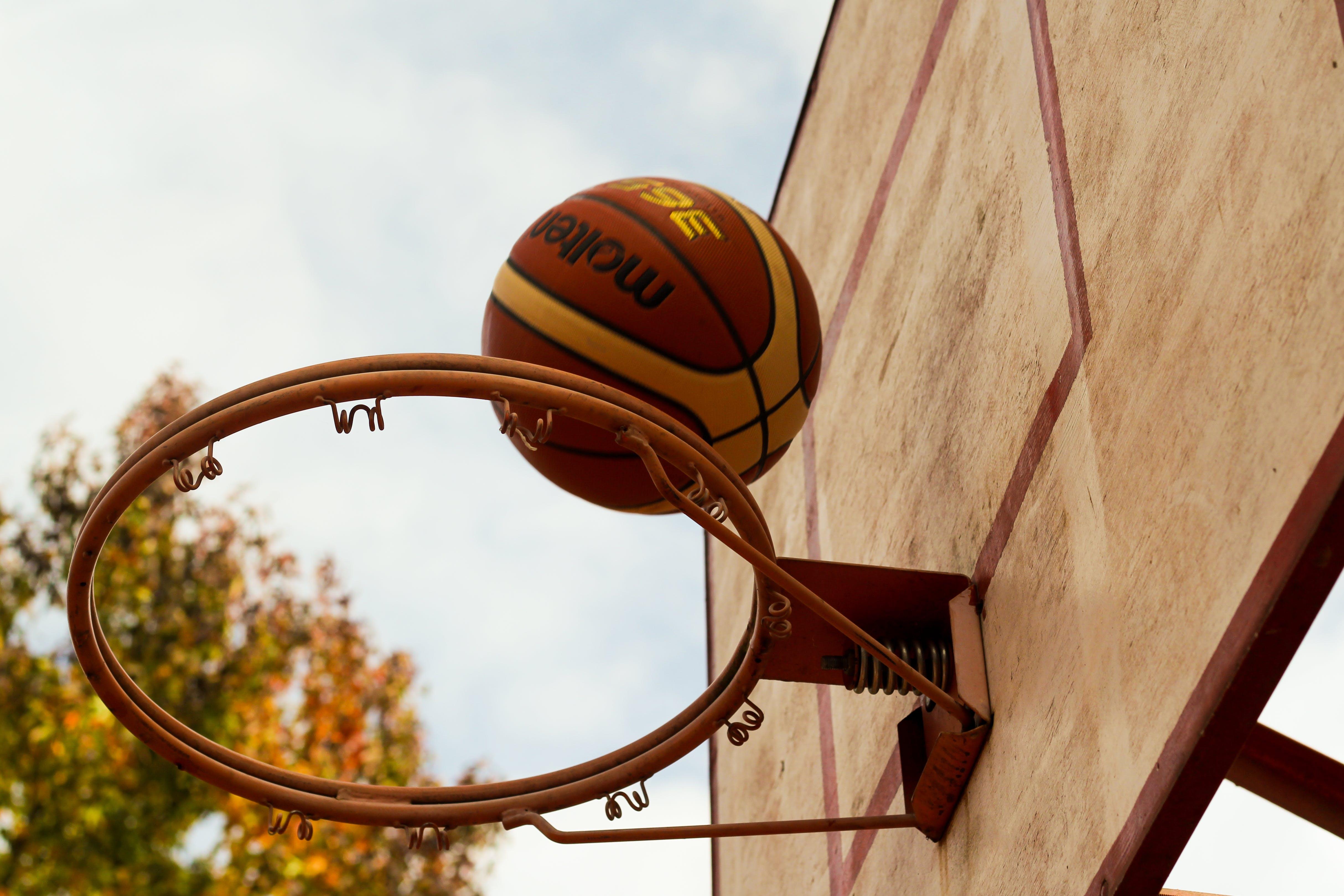 Brown Basketball Above Steel Basketball Hoop