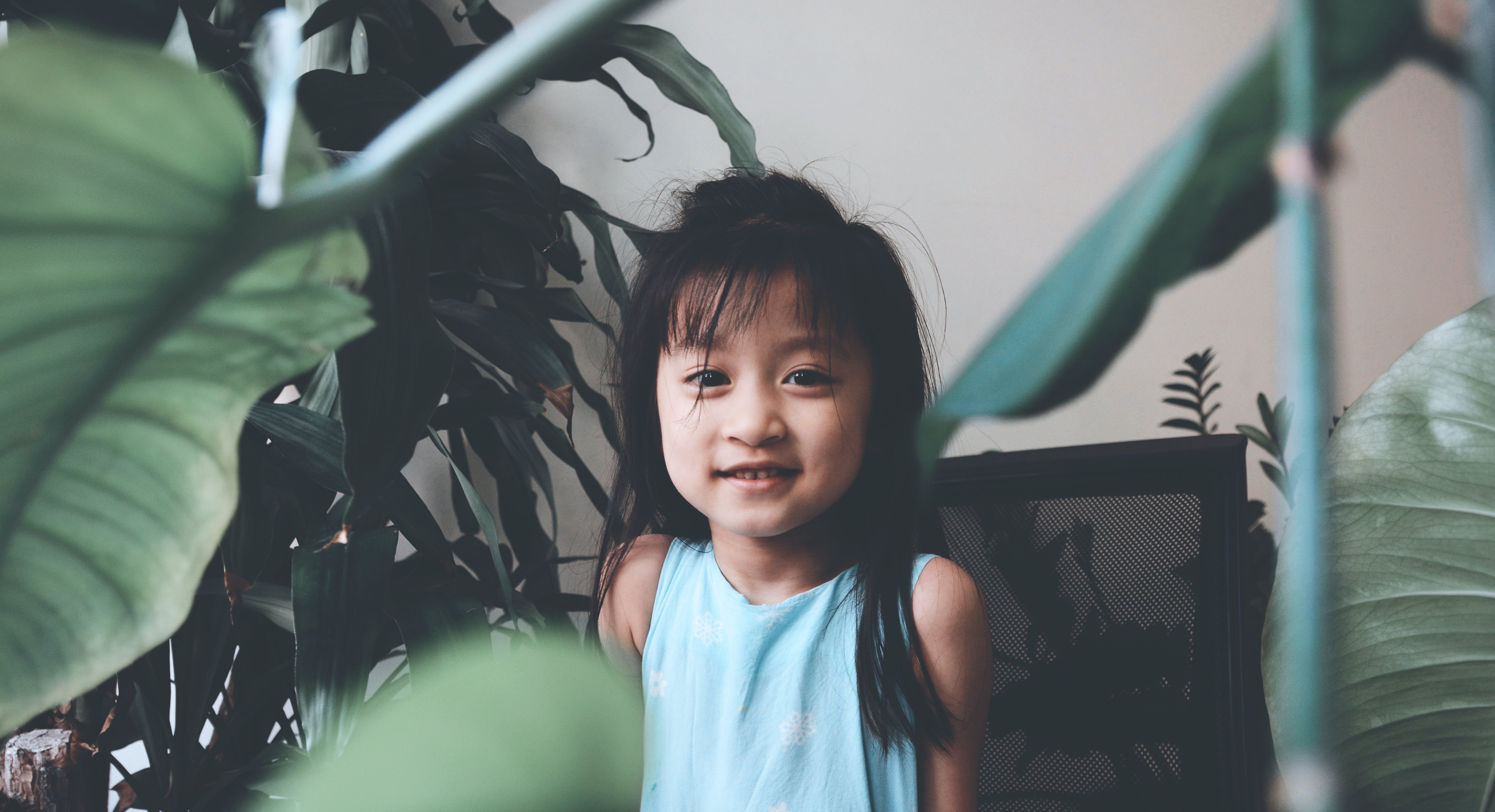 Smiling Girl Wearing Teal Tank Top Surrounded by Plants